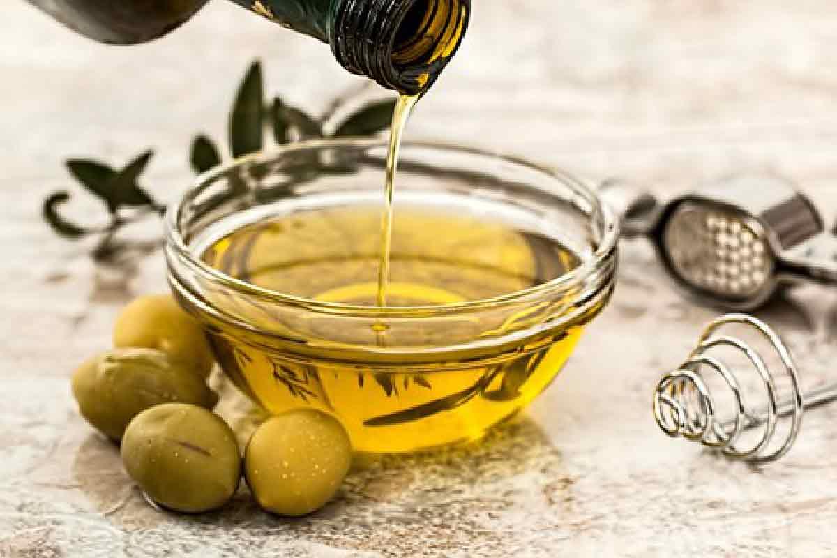 olio d'oliva ripreso in primo piano mentre viene versato in una ciotola