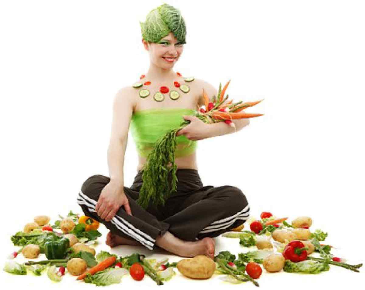 una donna ripresa mentre è ricoperta di verdure e ortaggi