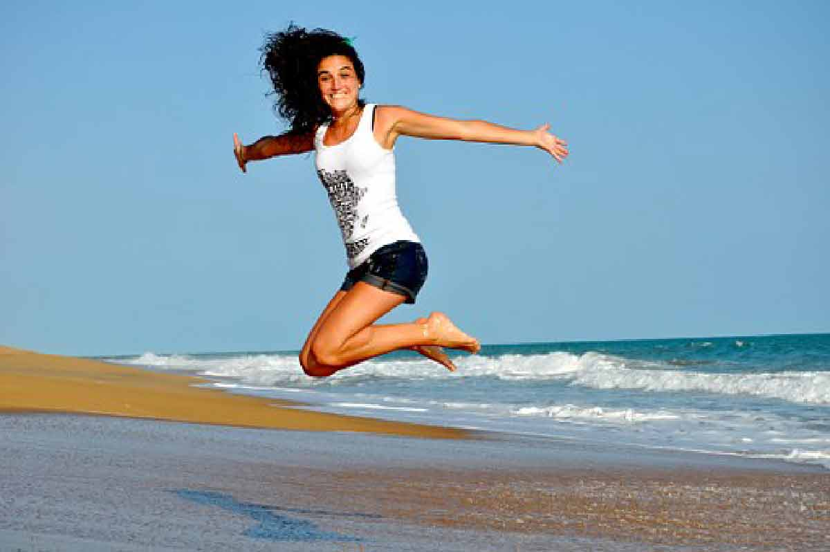 una donna salta sorridente in riva al mare