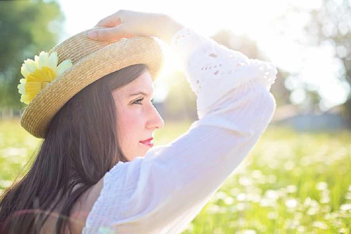 una donna viene ripresa mentre posa di profilo in un prato con un cappello