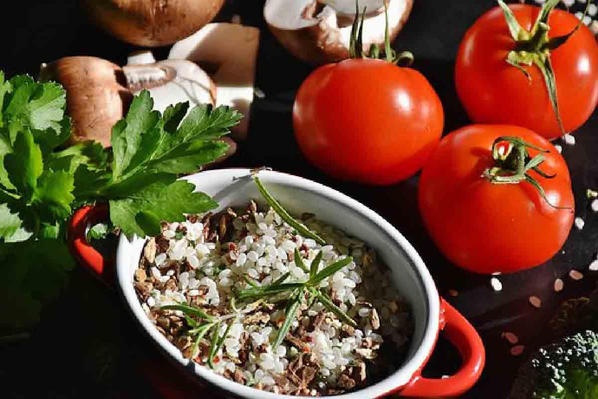 un piatto di riso e funghi con dei pomodori come contorno