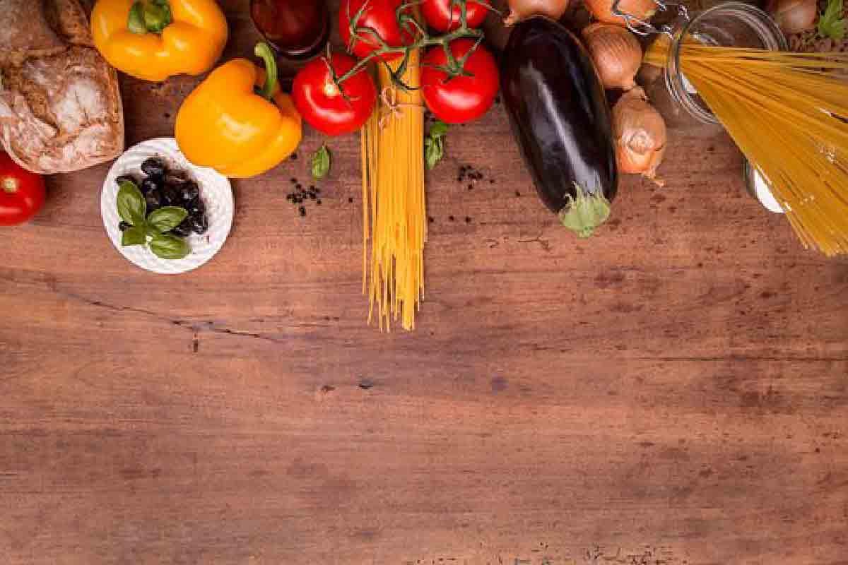 ortaggi, verdure e pasta ripresi dall'alto su un tavoliere di legno