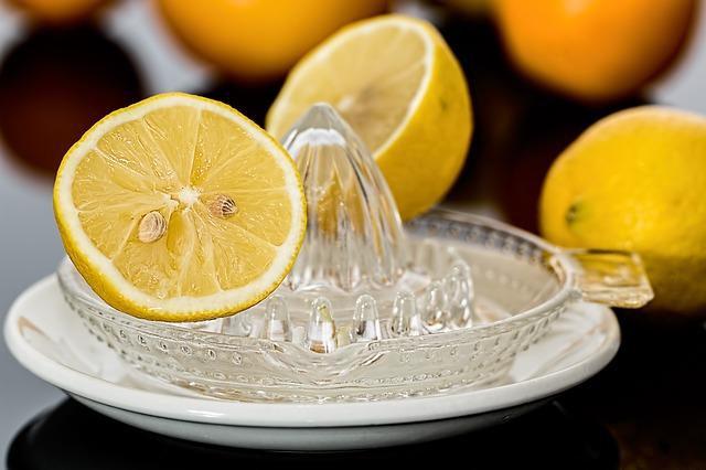 limoni in primo piano con uno spremiagrumi