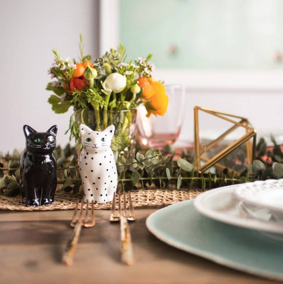 Photo of cute cat-shaped salt and pepper shakers on a decorated table.
