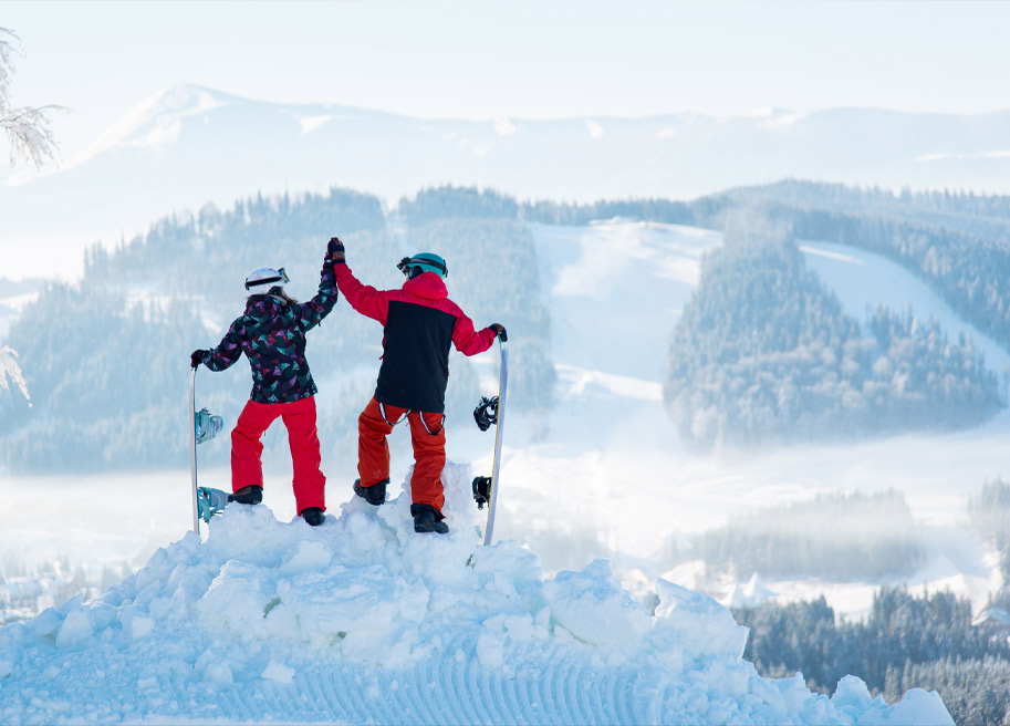 2 people highfiving each other on top of snow mountain with snowboards.