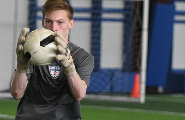 Goalkeeper in training, focused on a caught soccer ball.