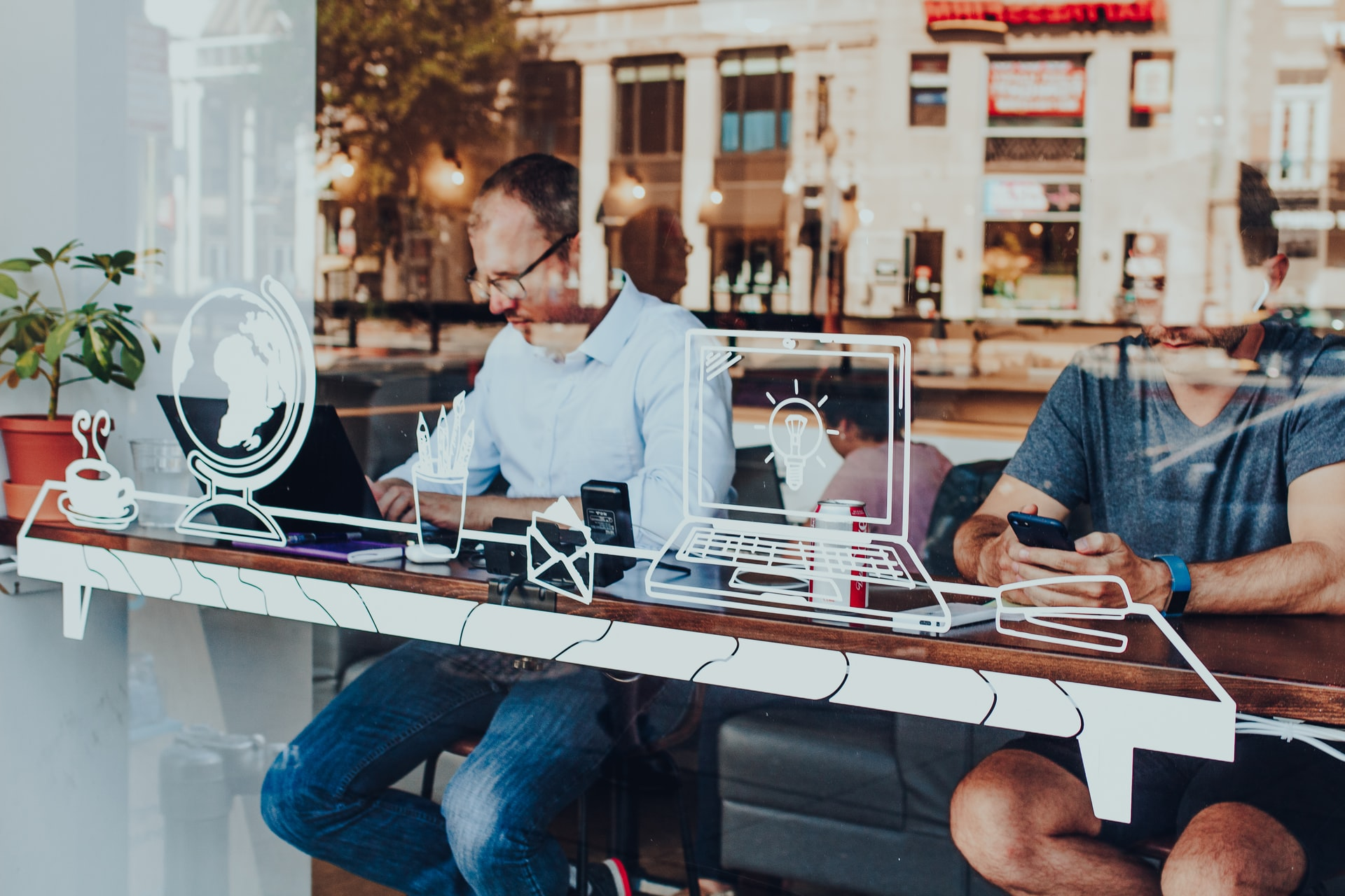 People sitting in a window using computers and smartphones