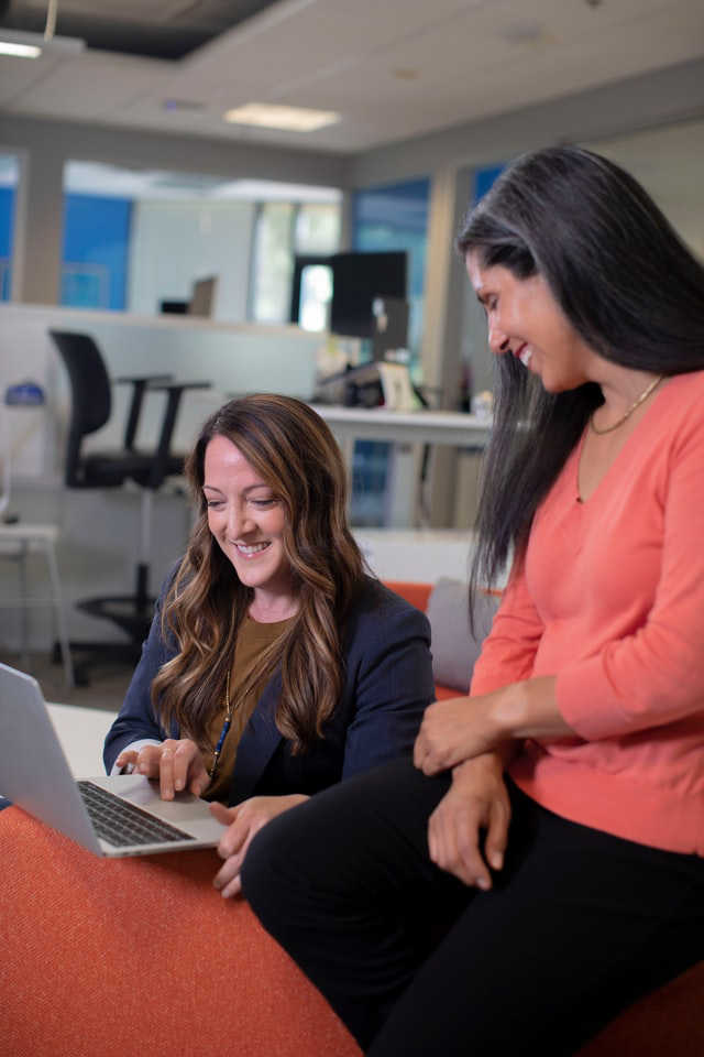 Women smiling in front of a laptop