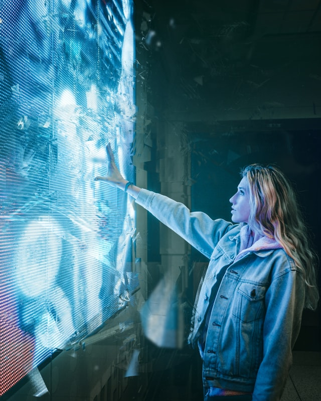 Photo of woman interacting with light installation