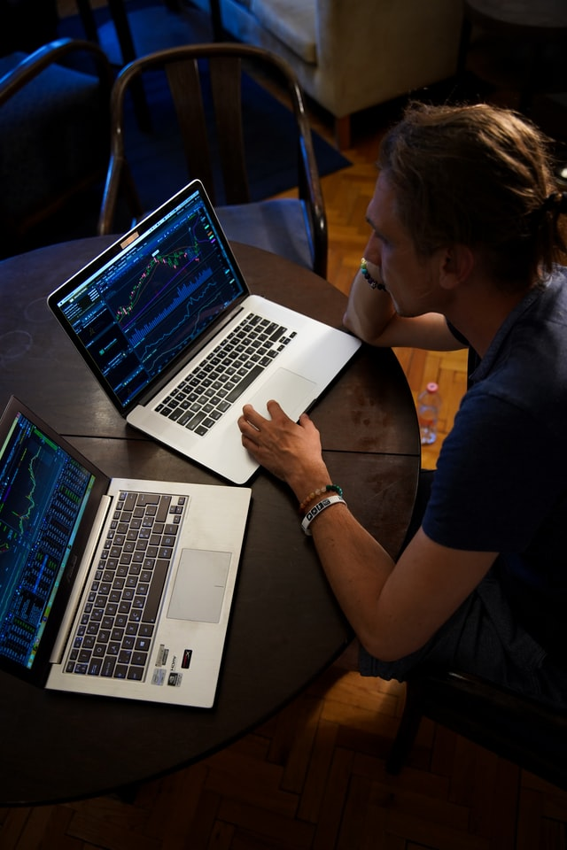 A man using two laptop computers