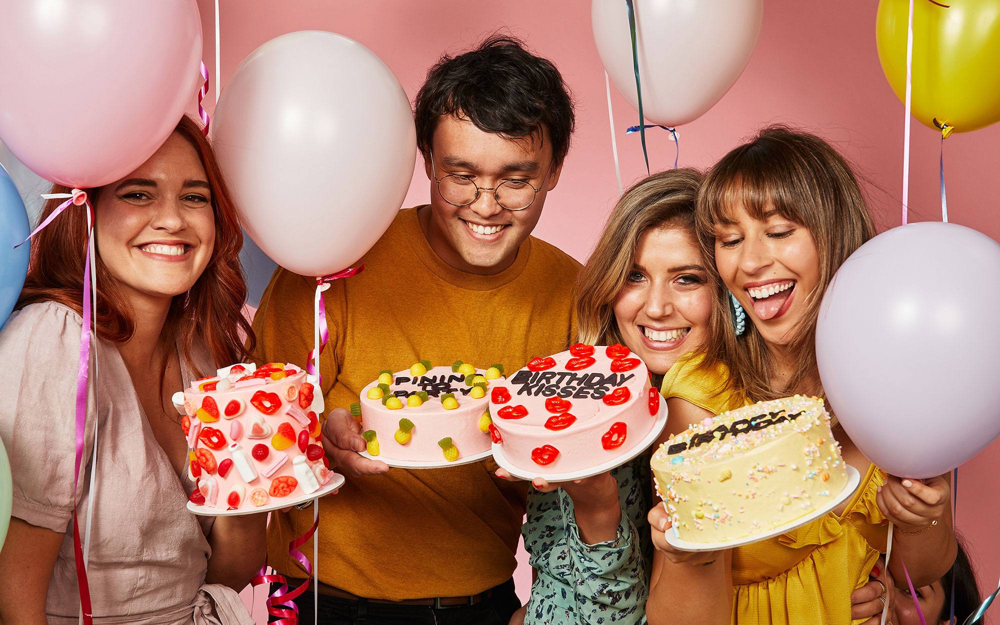 A photo showing three women and a man, surrounded by balloons and colourful cakes. Everyone is happy!