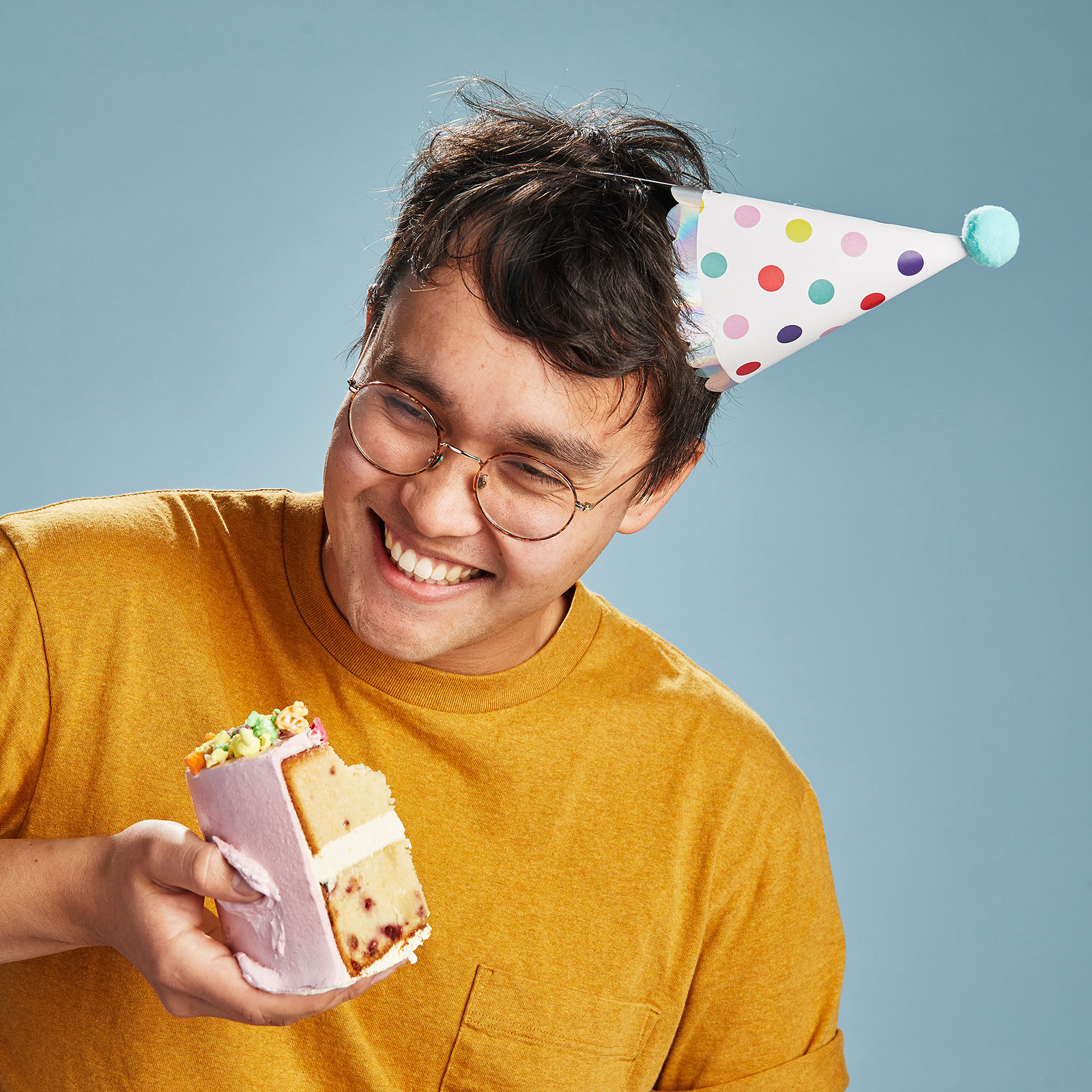 A photo of me in a yellow shirt, looking happy, with a slice of cake in my hand.