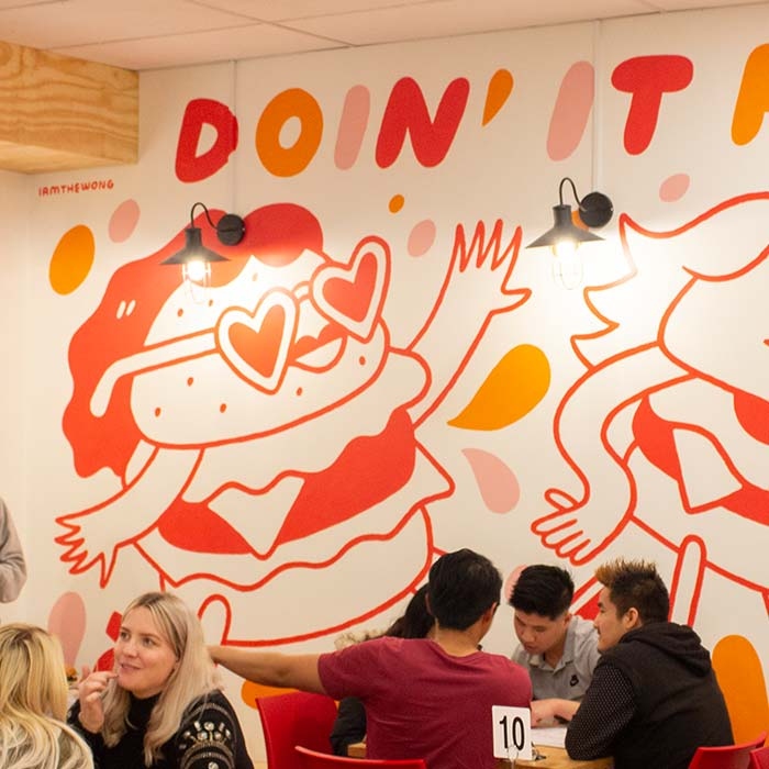 A photo of my mural at Johnny's Burgers, featuring cartoon burger ladies dancing.