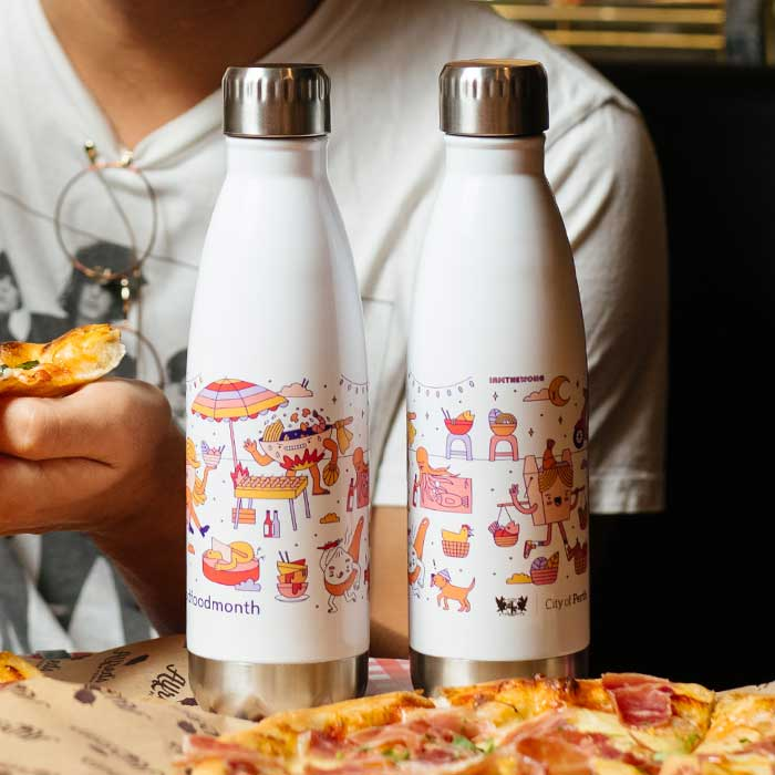 A photo of two bottles I designed for Good Food Month, with my hawkers market illustration wrapped around them.