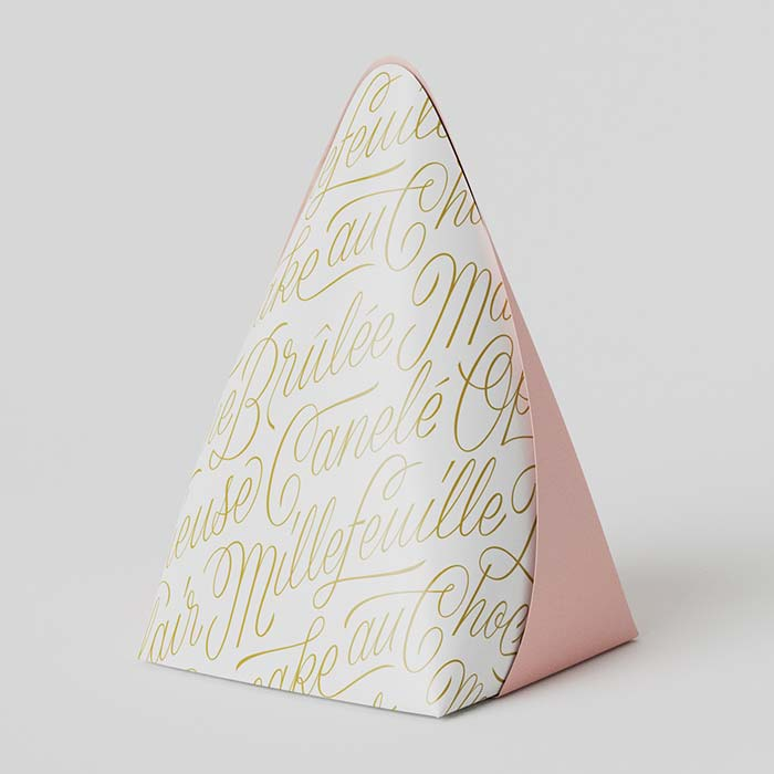 A photo of pastry packaging by Boite Cocotte, featuring my French script pattern.