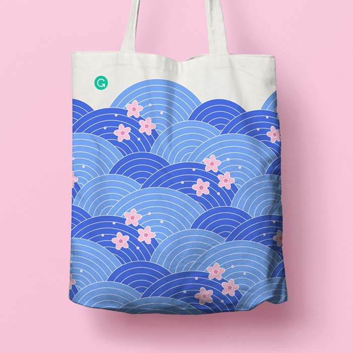 White tote bag with a blue Japanese wavy pattern, and pink sakura blossoms scattered over the top. Grammarly logo in top left corner.