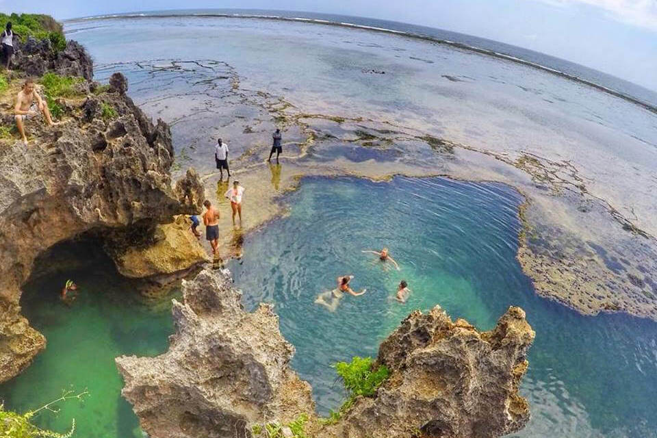 People jumping into a swimming hole in Kenya