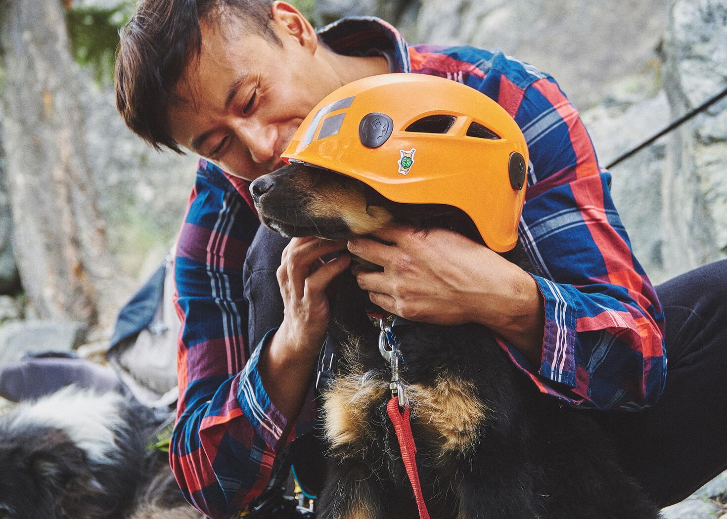 Man (Luca Li) in plaid shirt tying orange black diamond climbing helmet on black dog