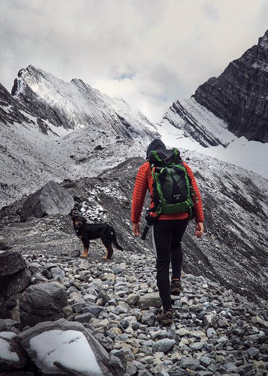 Hiker (Luca Li) in orange jacket with osprey exos backpack and black dog walking across old goat glacier
