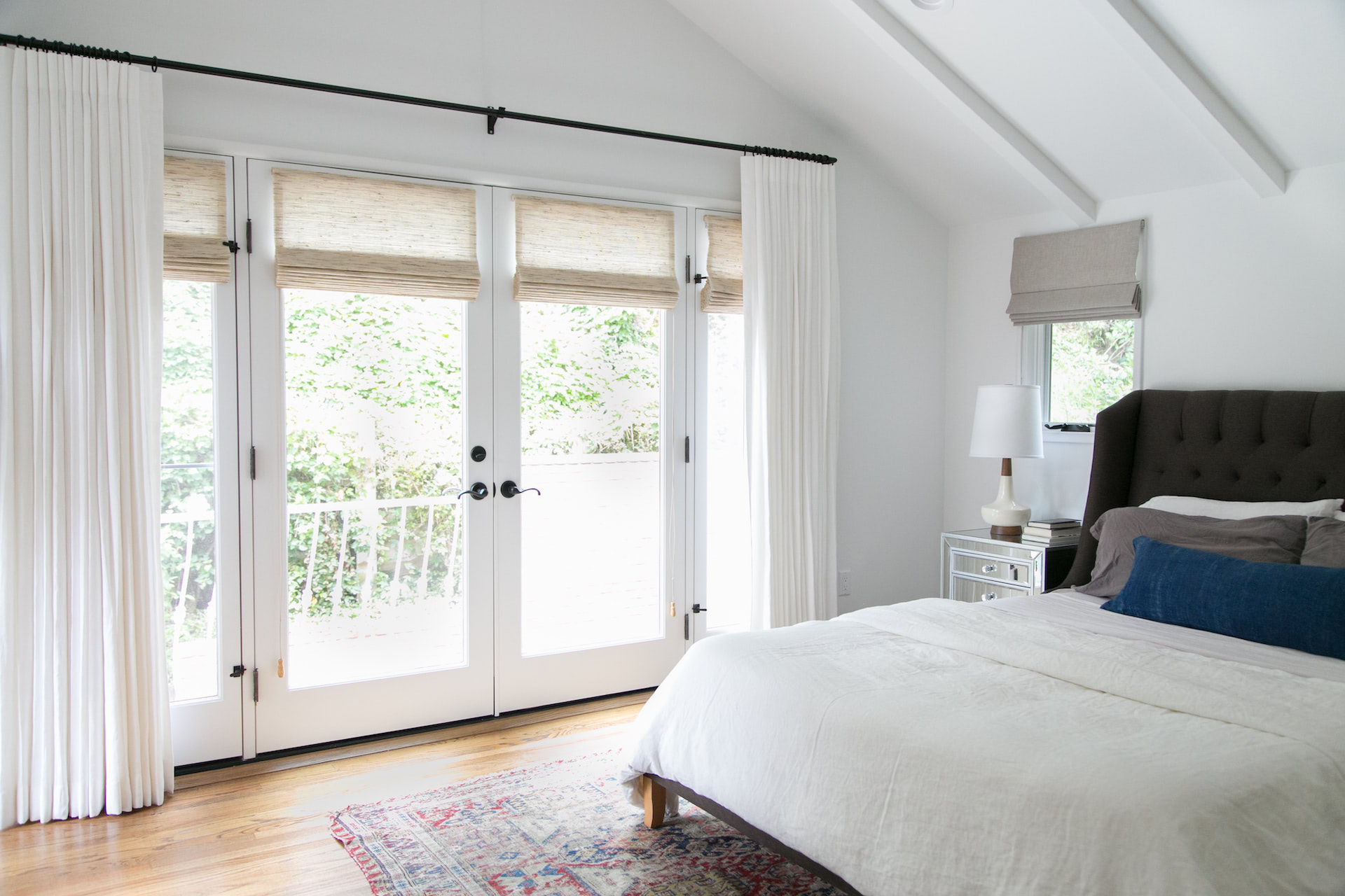 A bedroom with roman shades on a glass door and window, and white drapes on the window | Everhem