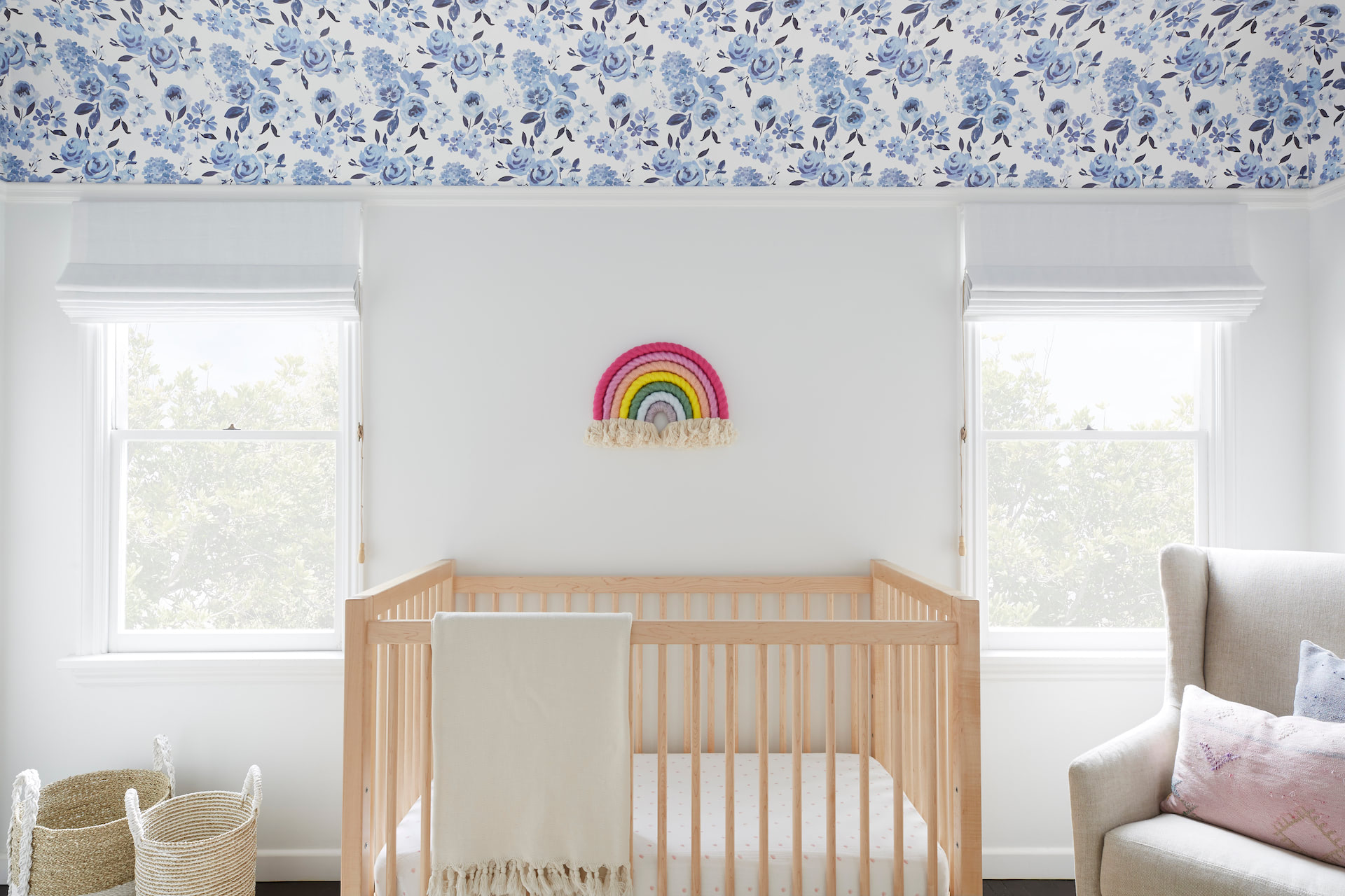 A nursery with custom window treatments covering two small windows | Everhem