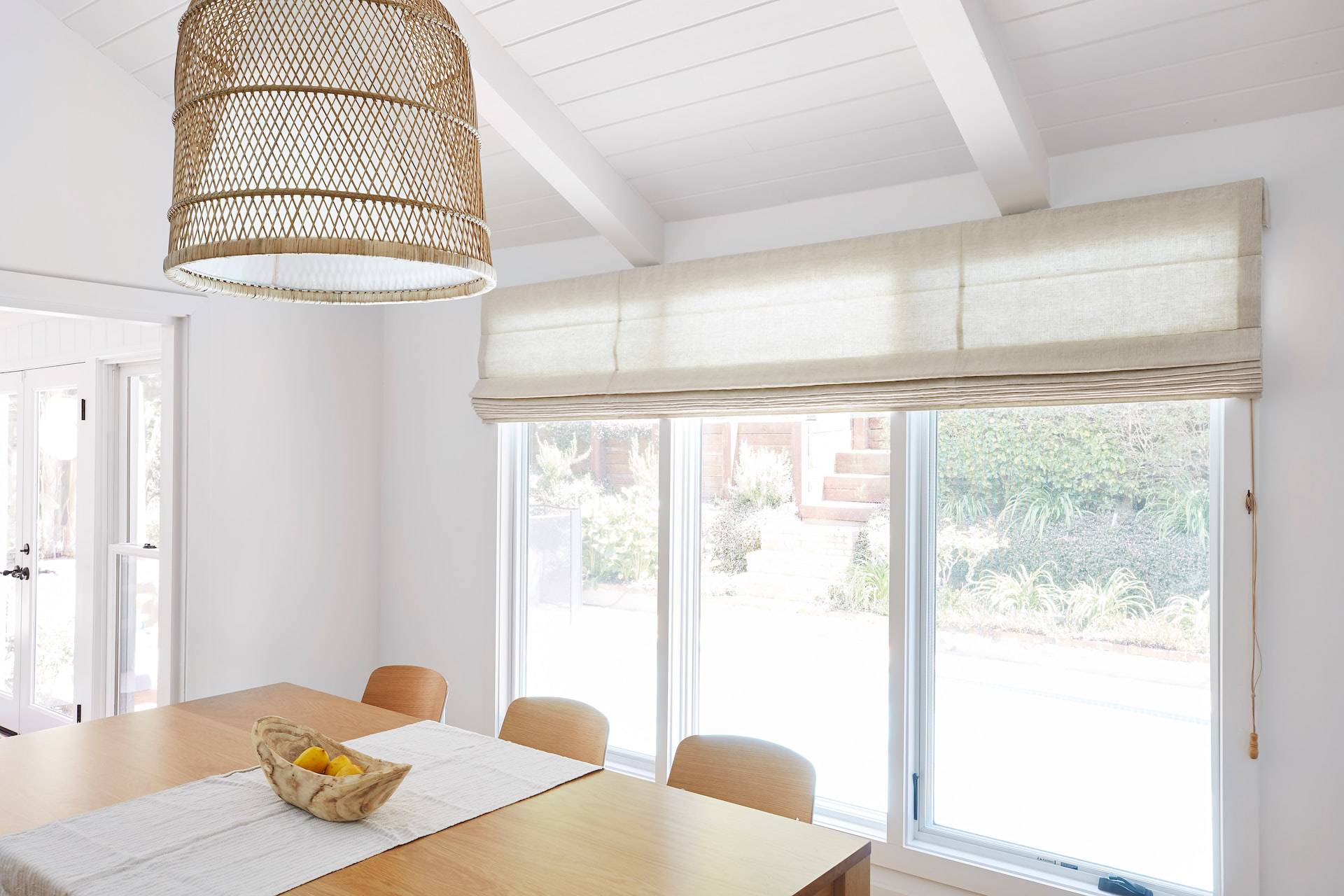 Roman shades raised to look outside a dining room window | Everhem