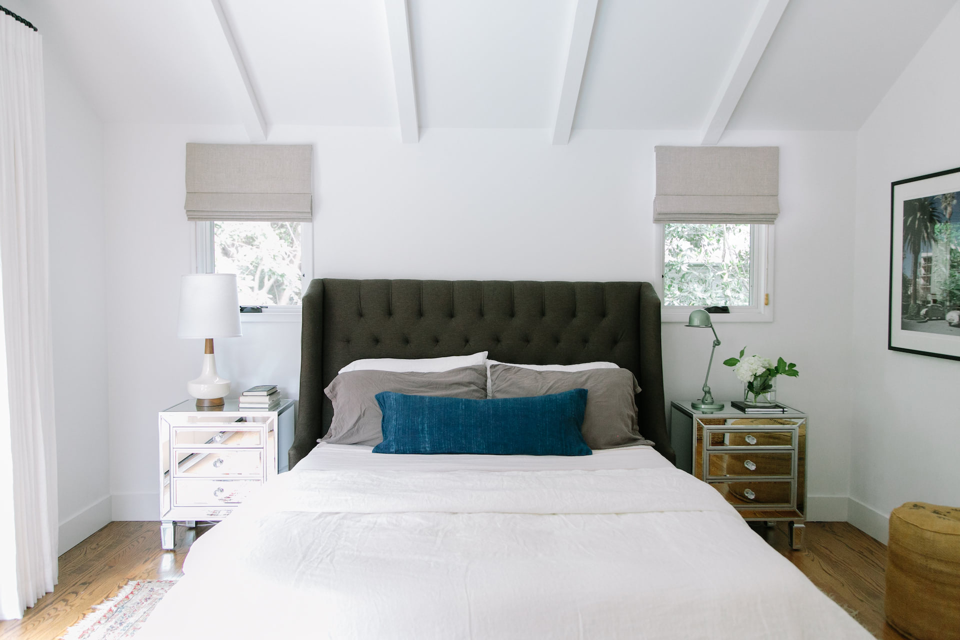 A bedroom with custom roman shades on two small windows next the the headboard | Everhem