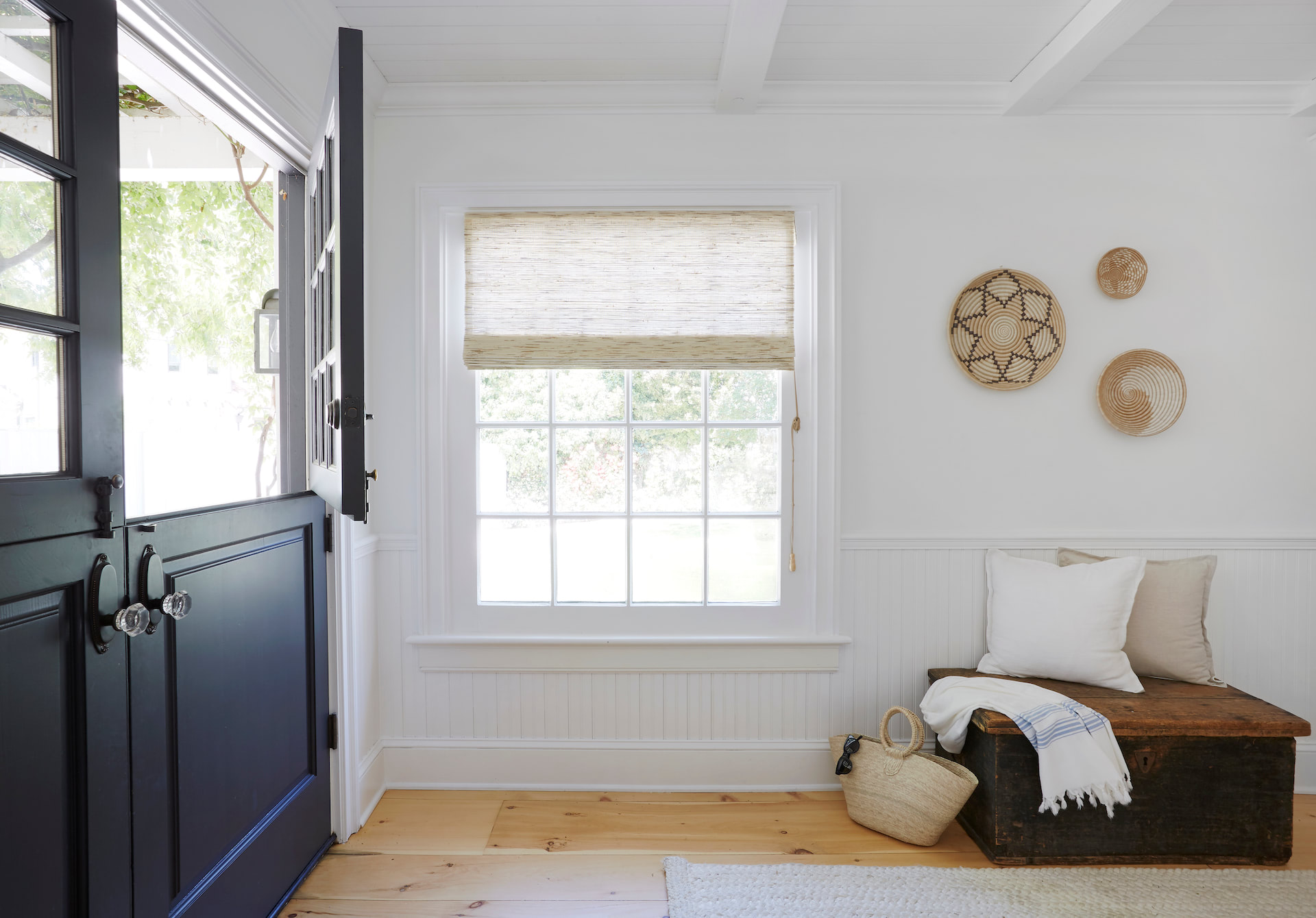 An entryway with a window covered by woven woods | Everhem