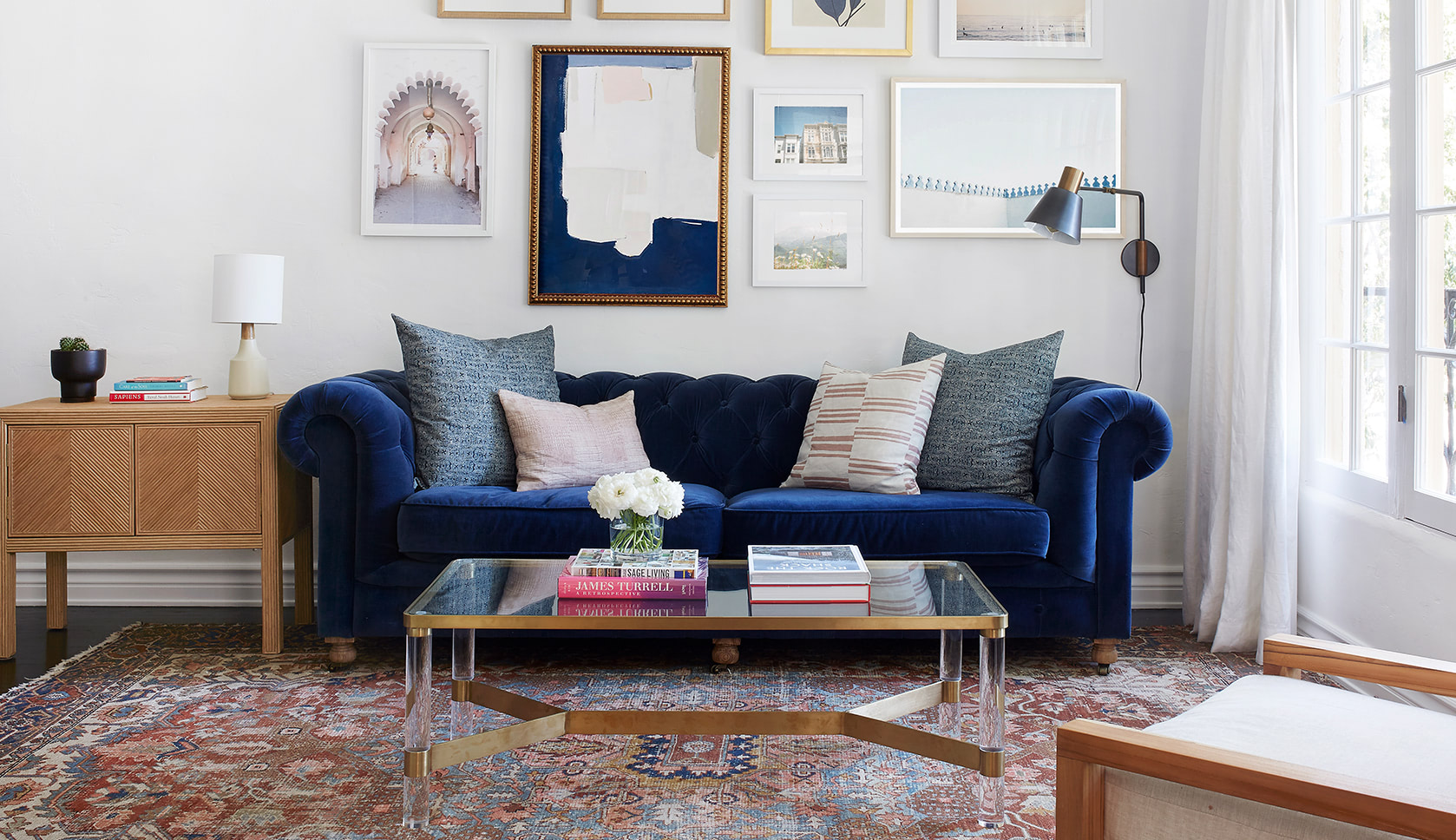 A living room with a blue couch and custom window treatments   Everhem