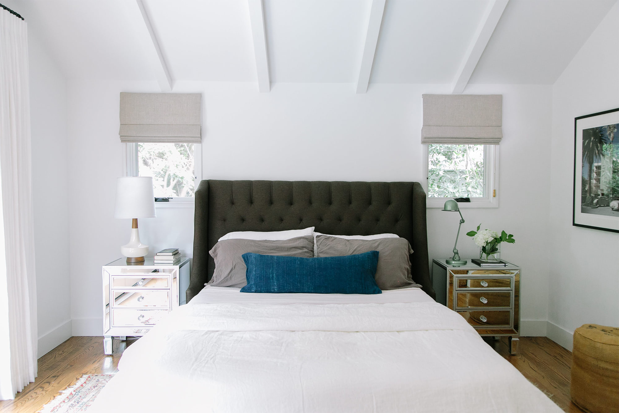 A master bedroom feels expansive with white walls, neutral bedding and off-white Roman shades