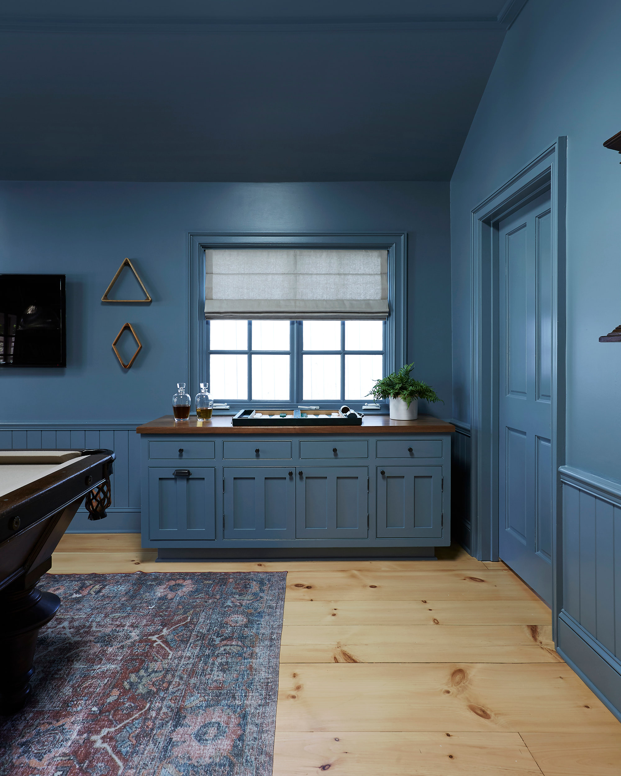 A Roman shade is mounted inside to accentuate the molding and craftmanship of this cool-blue rec room.