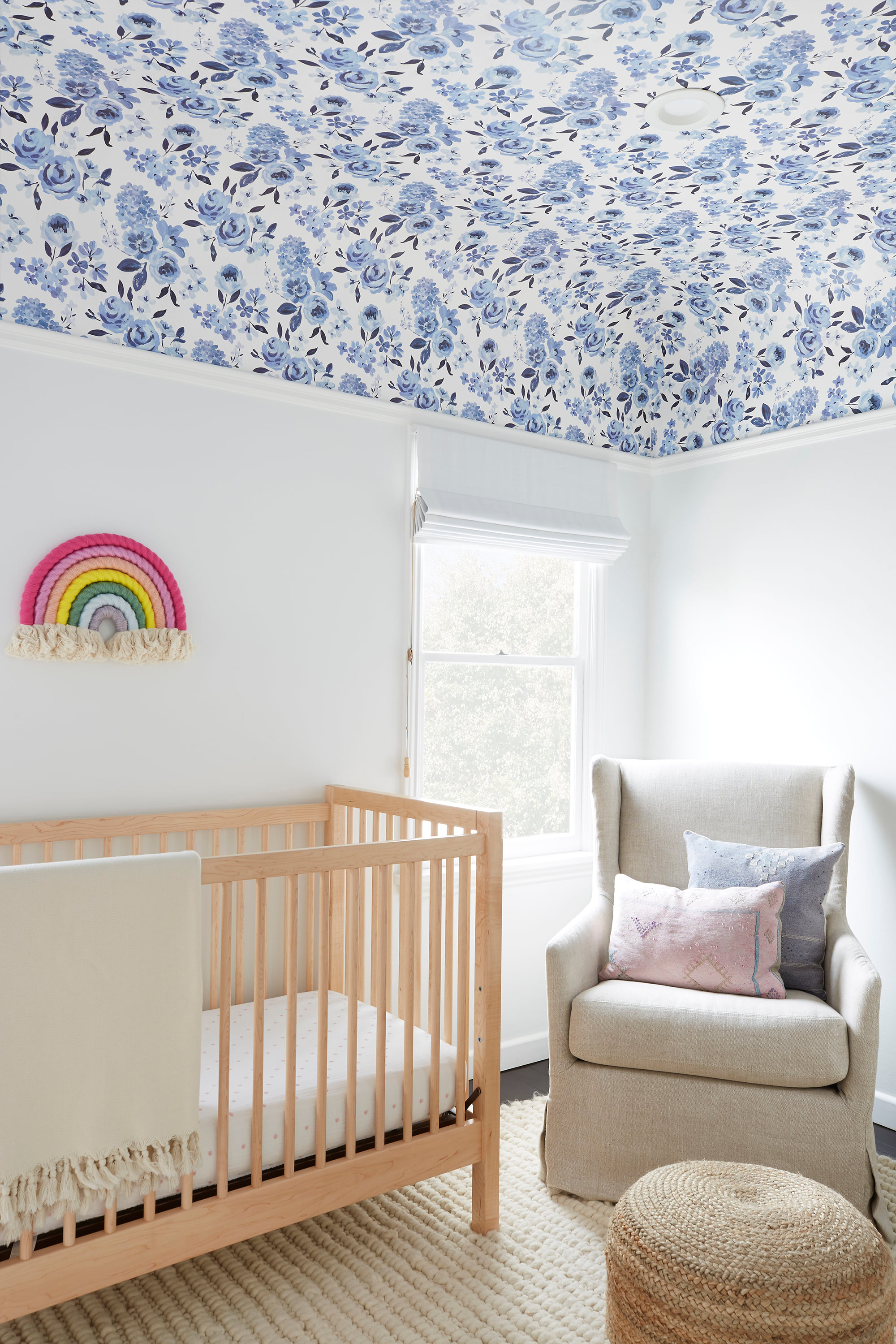 A white-walled nursery has white Roman shades to keep your focus on the blue floral ceiling paper.