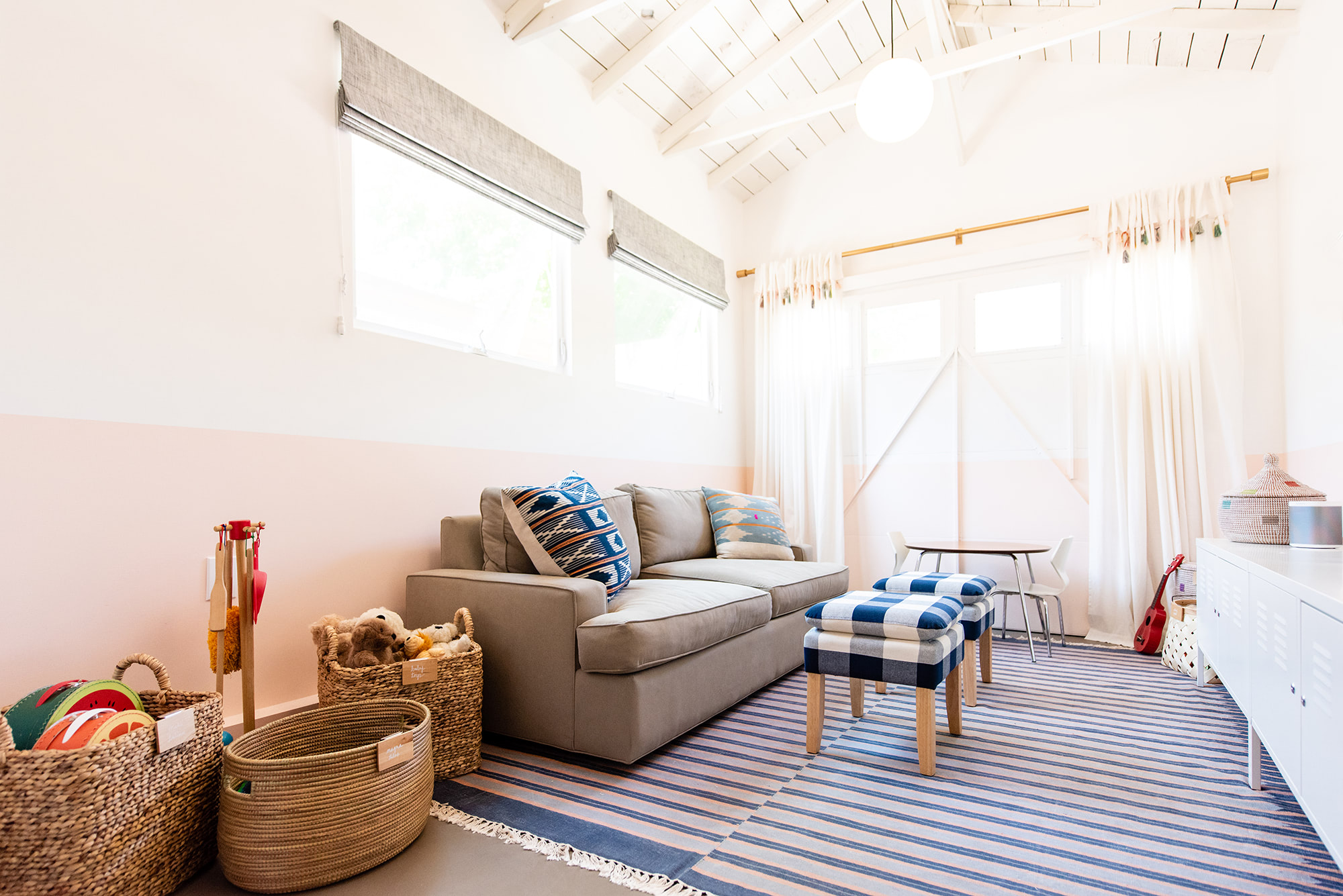 Light, linen Roman shades let the blue-striped rug and patterned pillows pop in this play room.