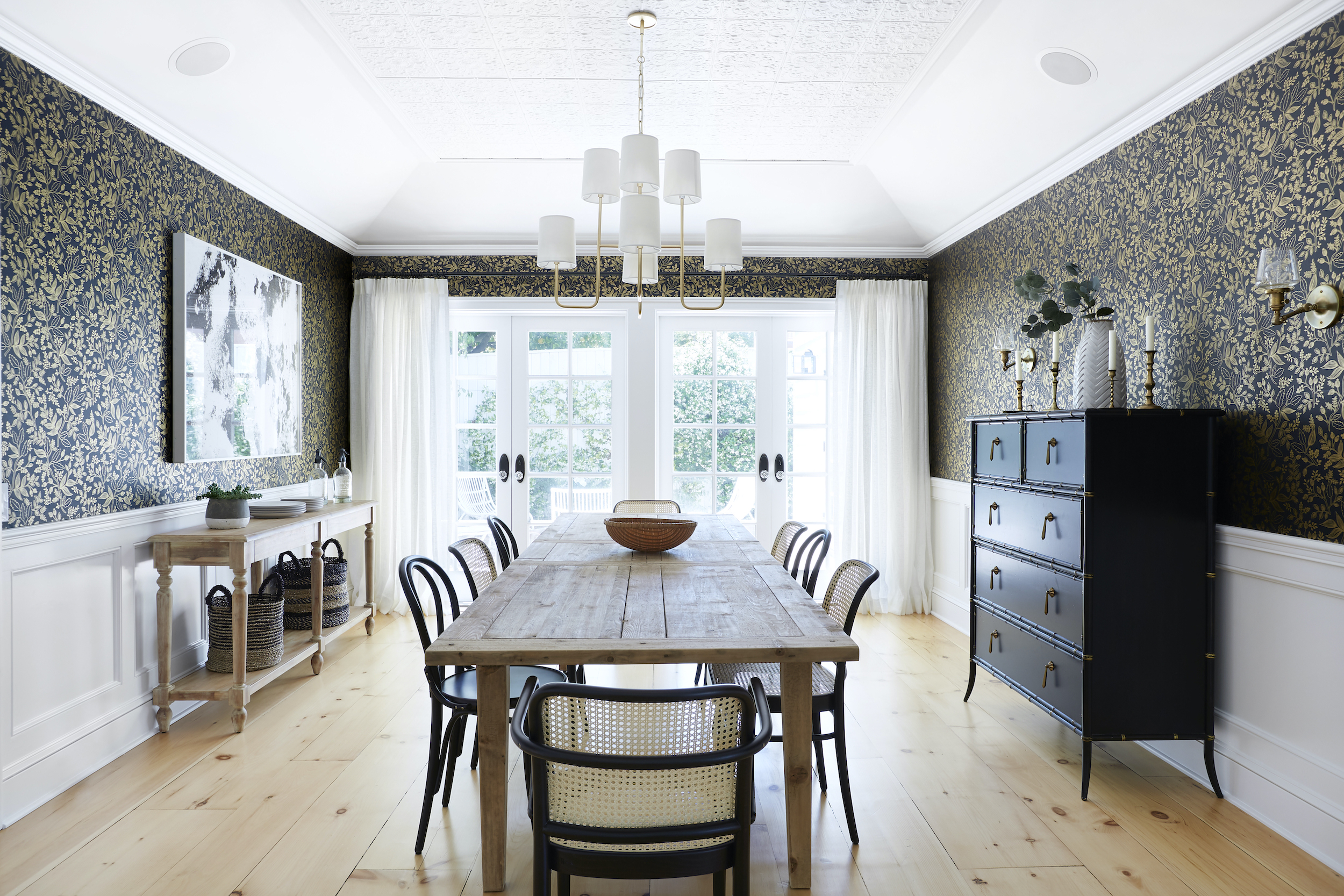 White drapery in a dining room for two sets of French doors hang down to the light wood floors
