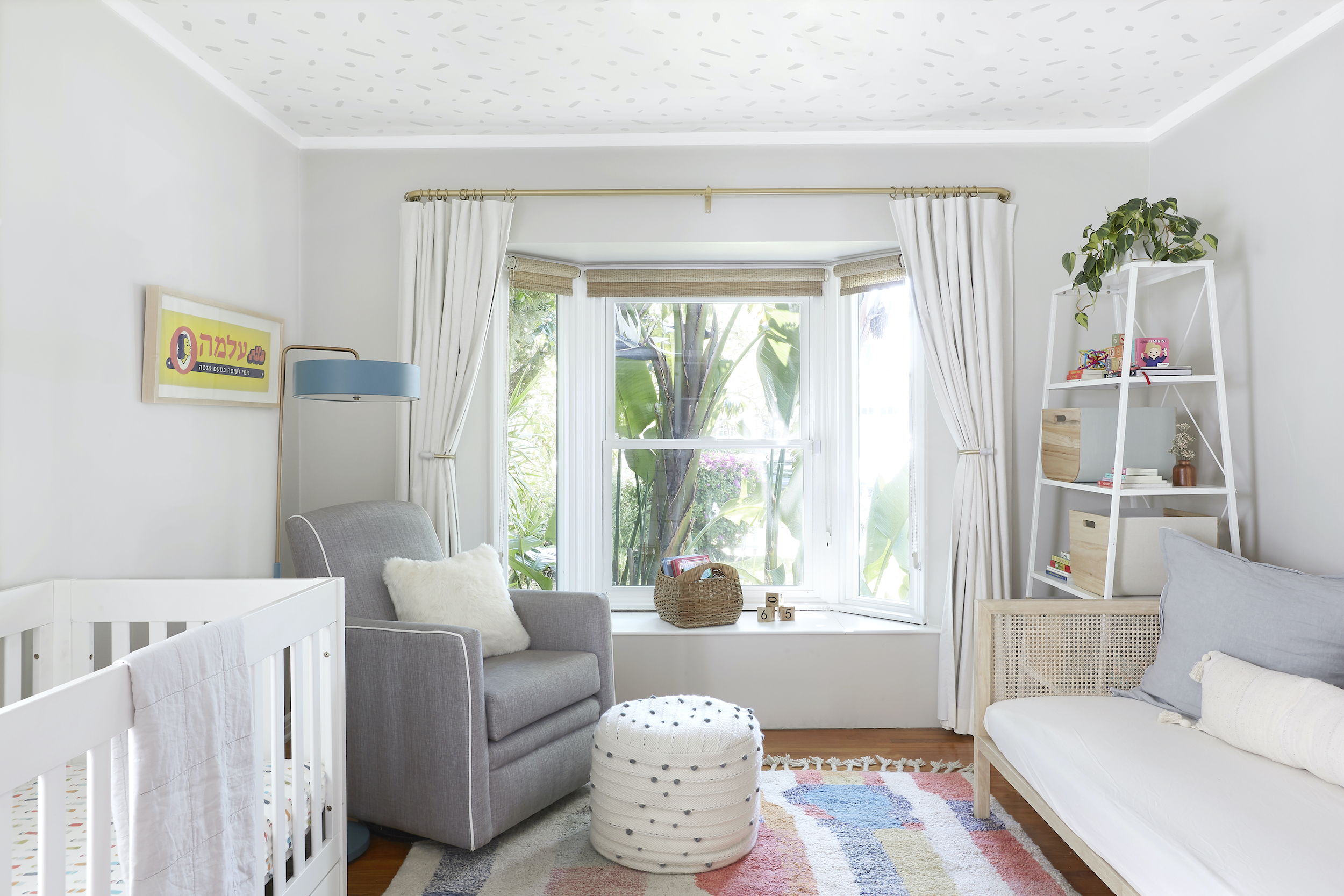 White drapes and woven shades in bay window make it easy to adjust natural lighting in nursery