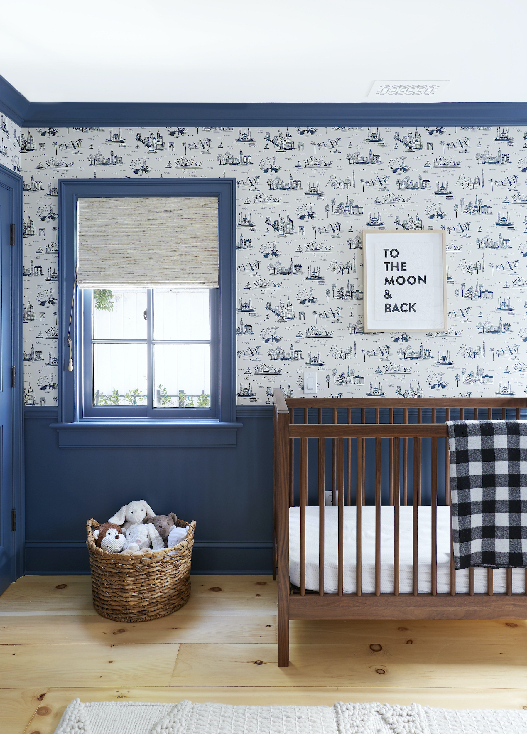 Woven shades are safe & stylish nursery window treatments against a blue trim & patterned wallpaper