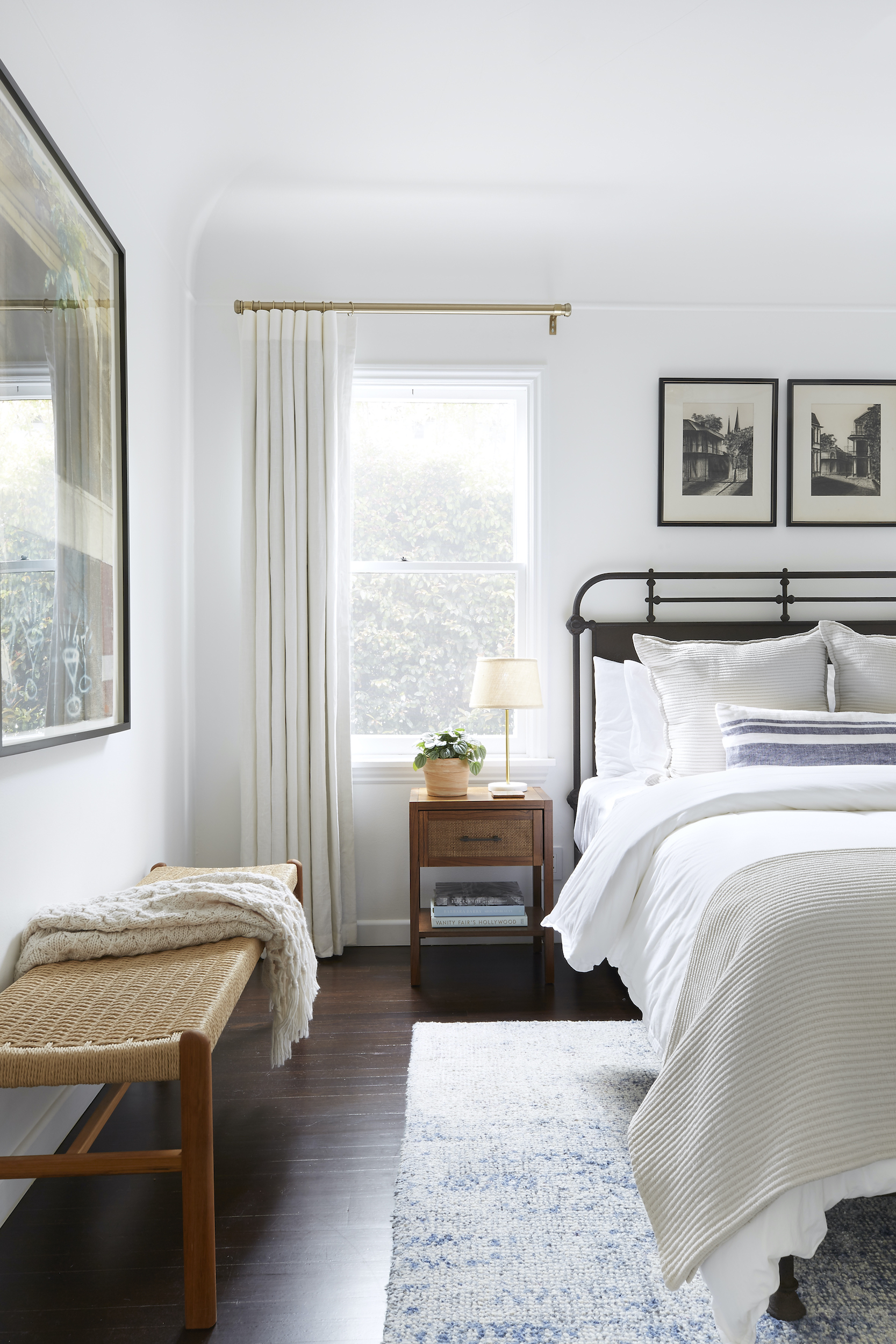 The best fabric for drapery will hang neatly like these white linen curtains in a neutral bedroom