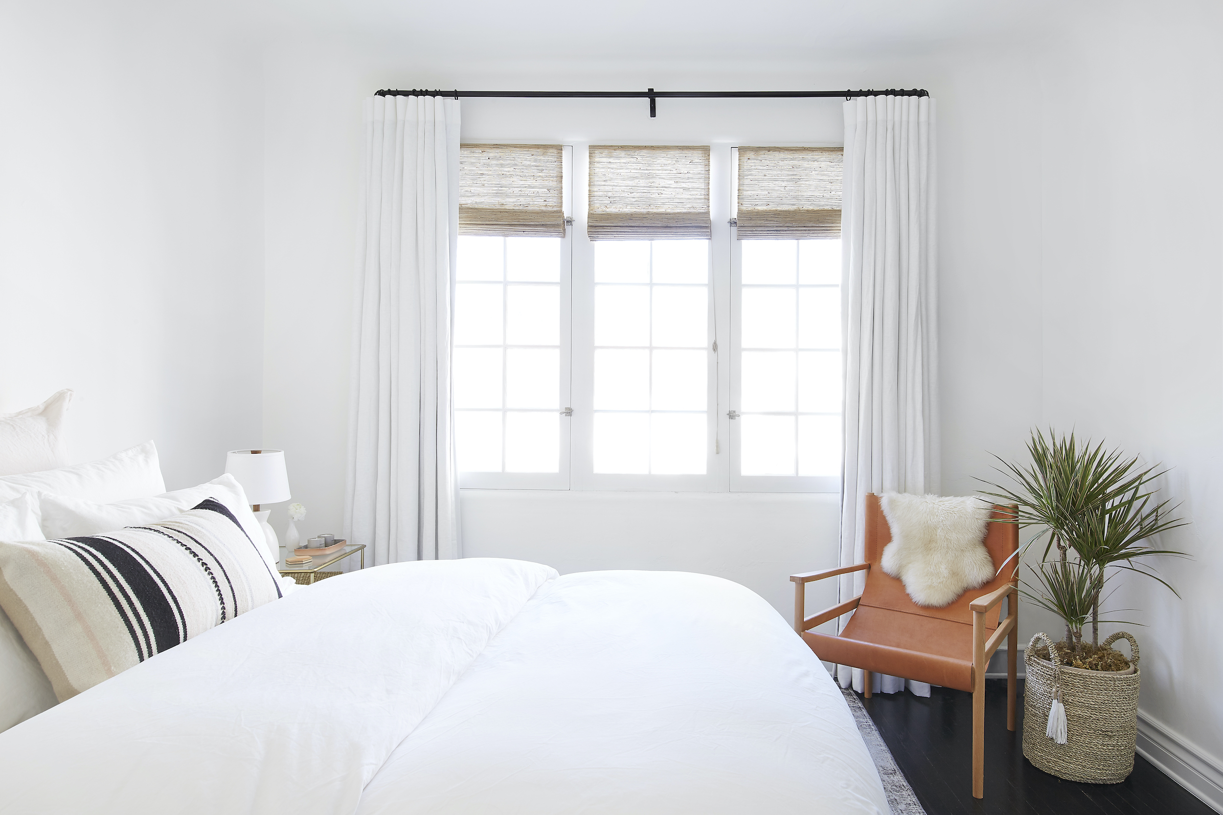Everhem's linen drapes and woven woods cover three side-by-side windows in a neutral-theme bedroom