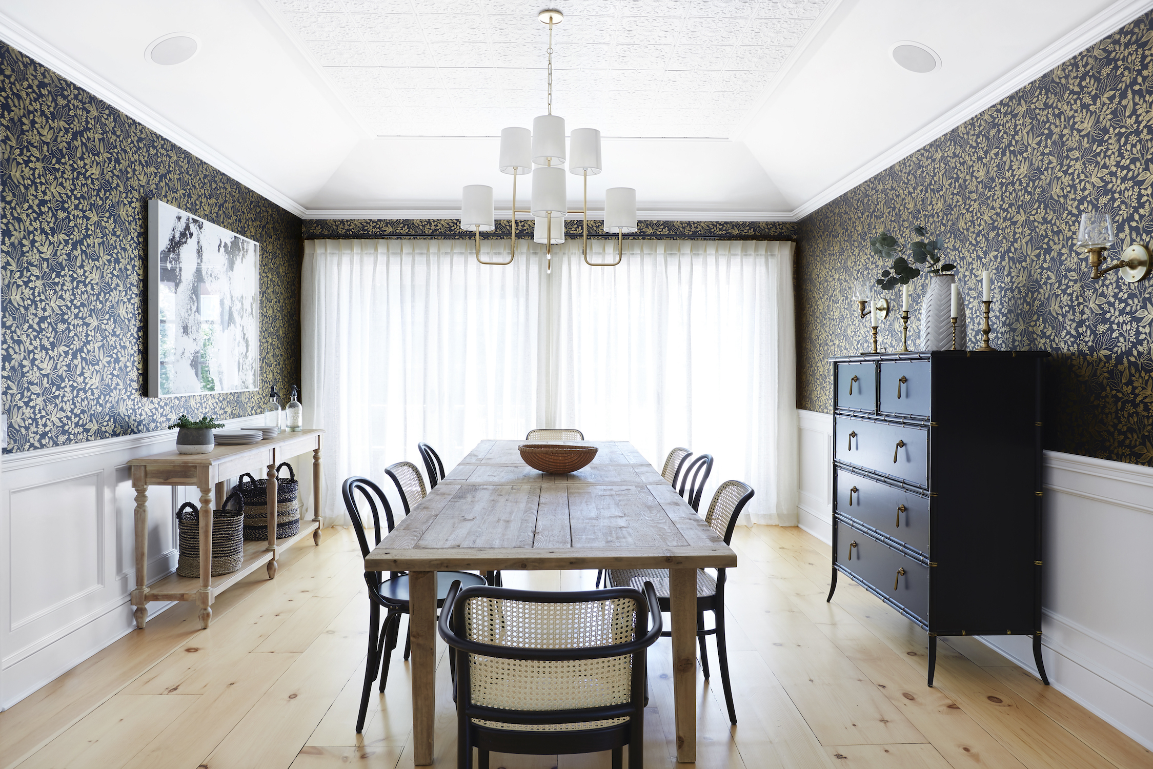 Closed linen drapes control the lighting and set the mood in a neutral dining room.