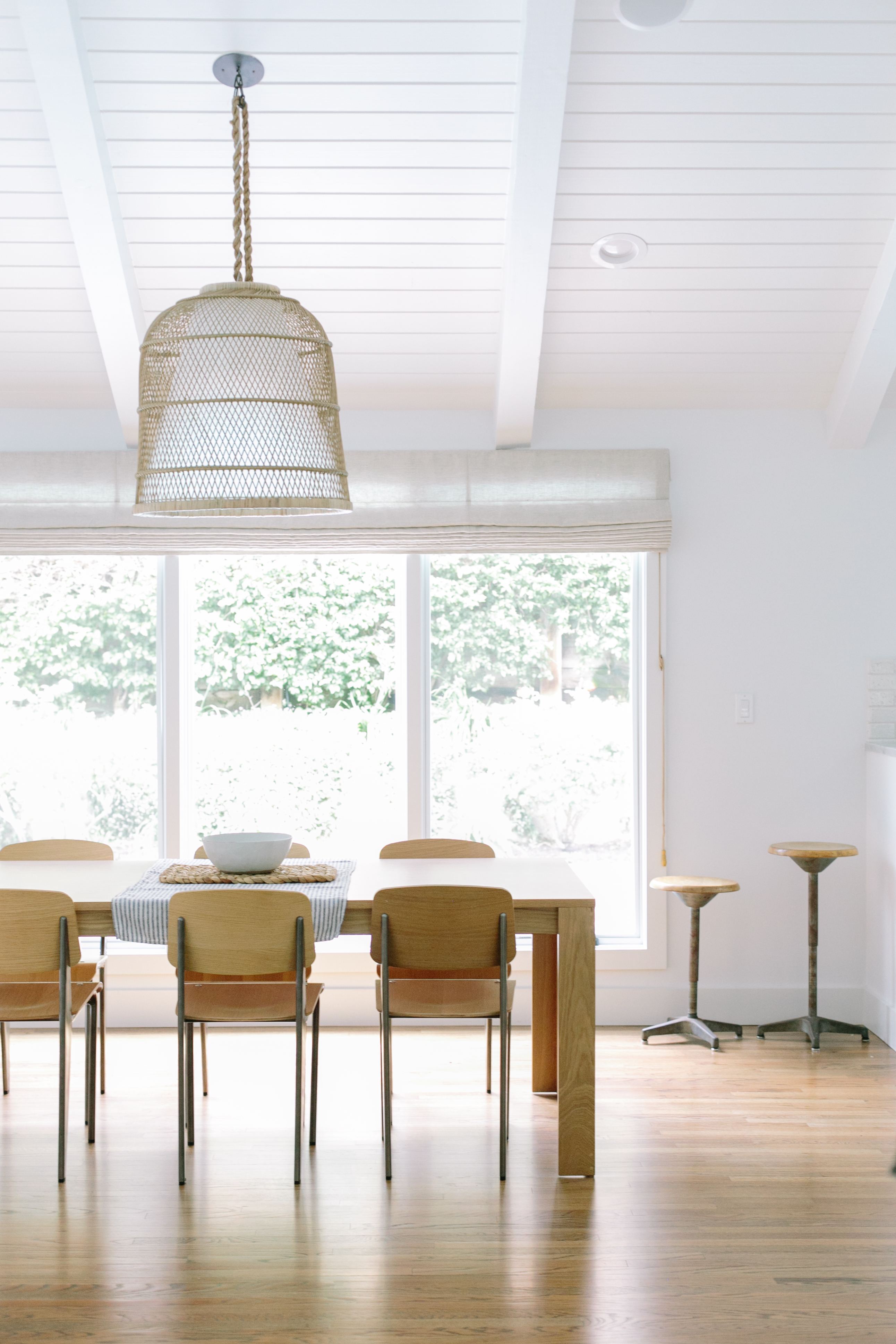 Everhem Roman shades hang in mid-century modern dining room with oversized pendant light.