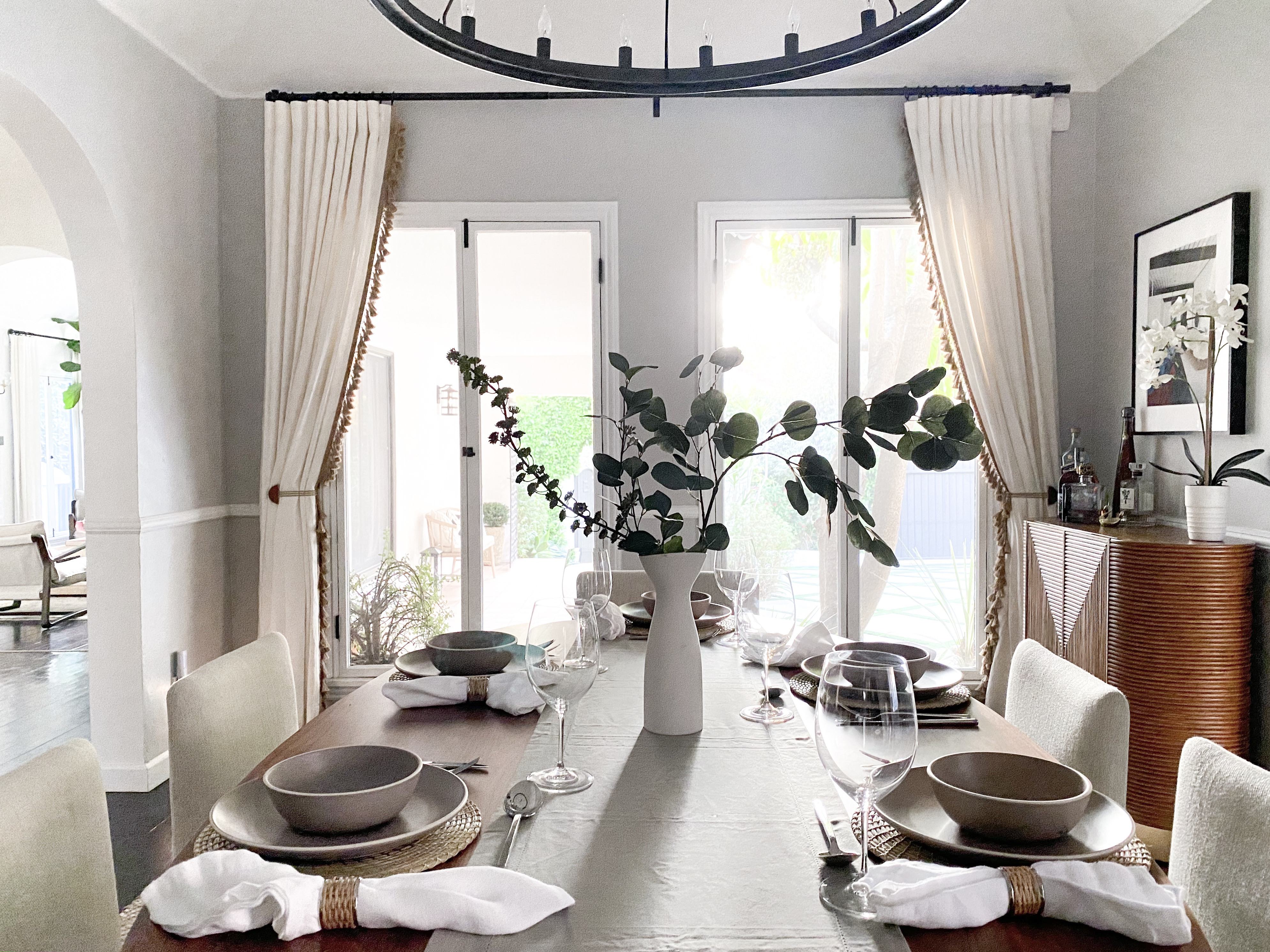 Dining room decor tricks: a table set with plates, cloth napkins, a table runner & faux flowers.