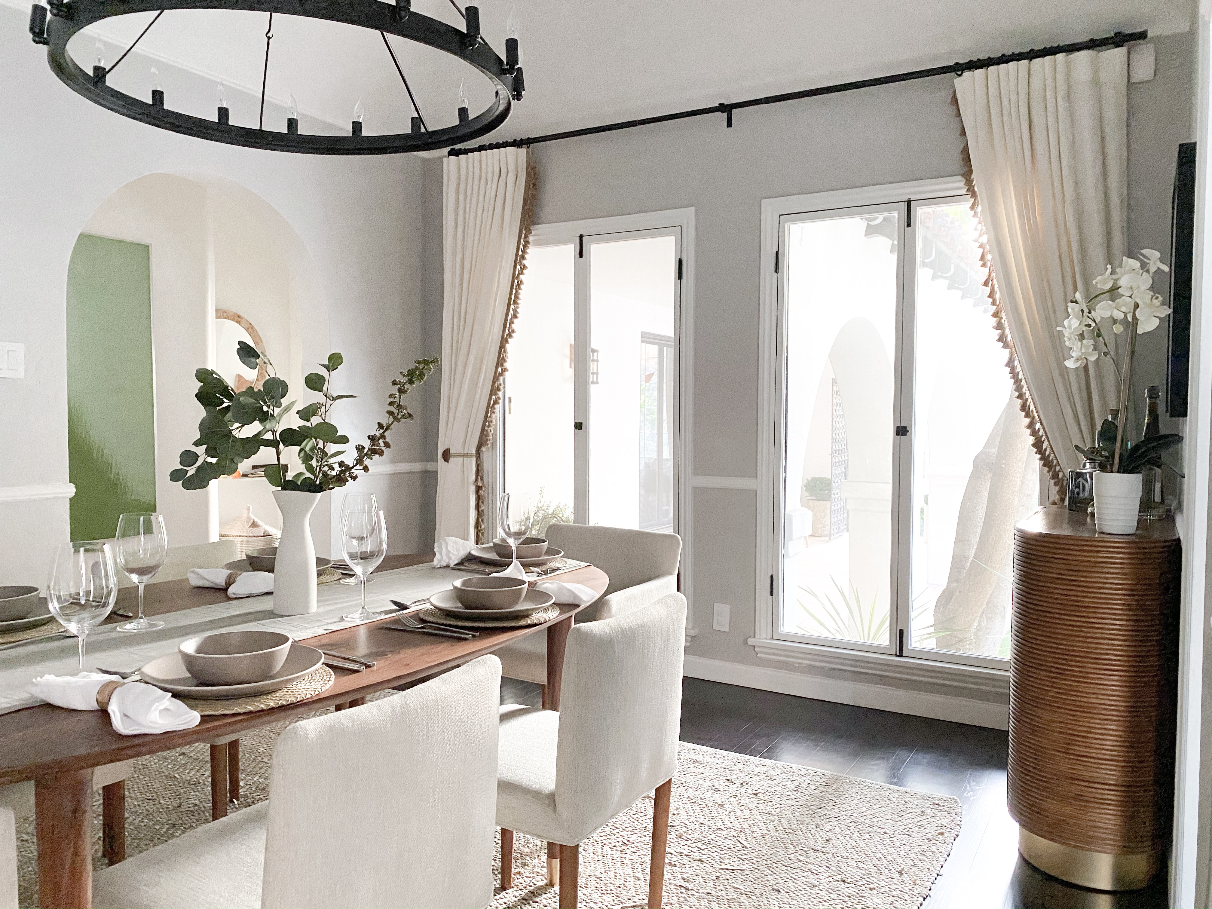 Modern dining room with a pre-set table, area rug and Everhem linen drapery