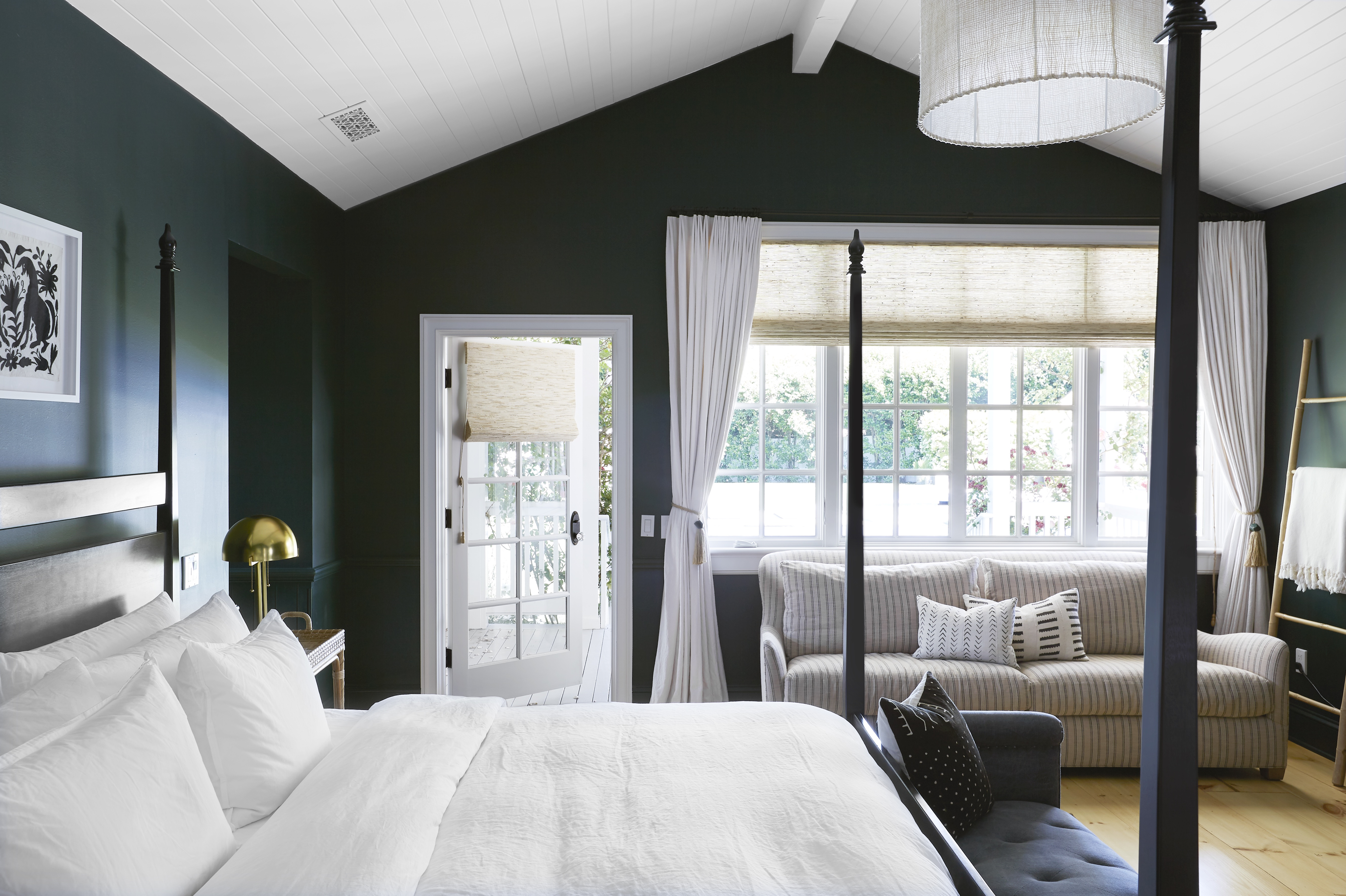 Pair large window coverings, like woven woods and drapery to add privacy to a bedroom
