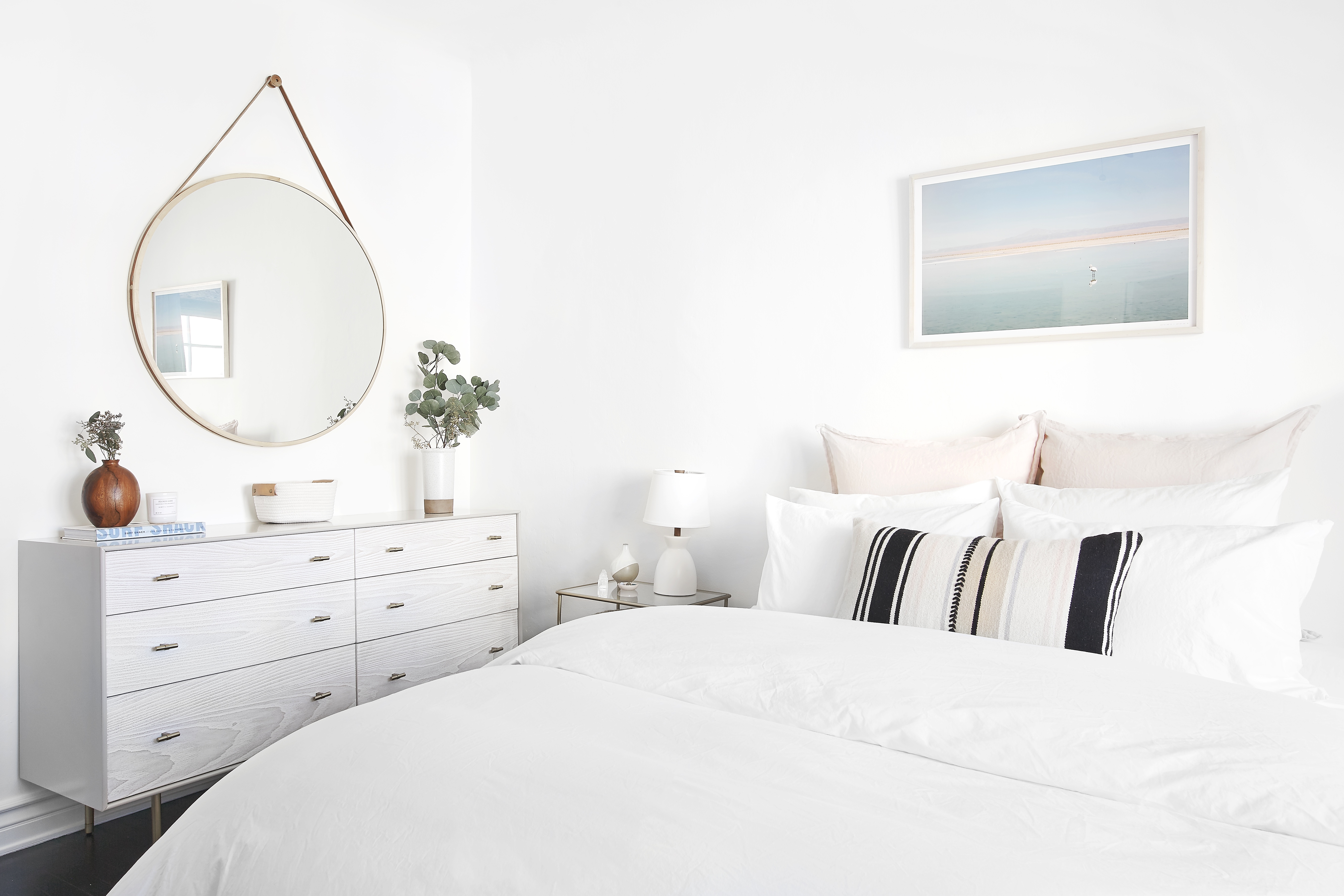 A sleep sanctuary with plush white bedding, minimal décor and fresh eucalyptus in vase