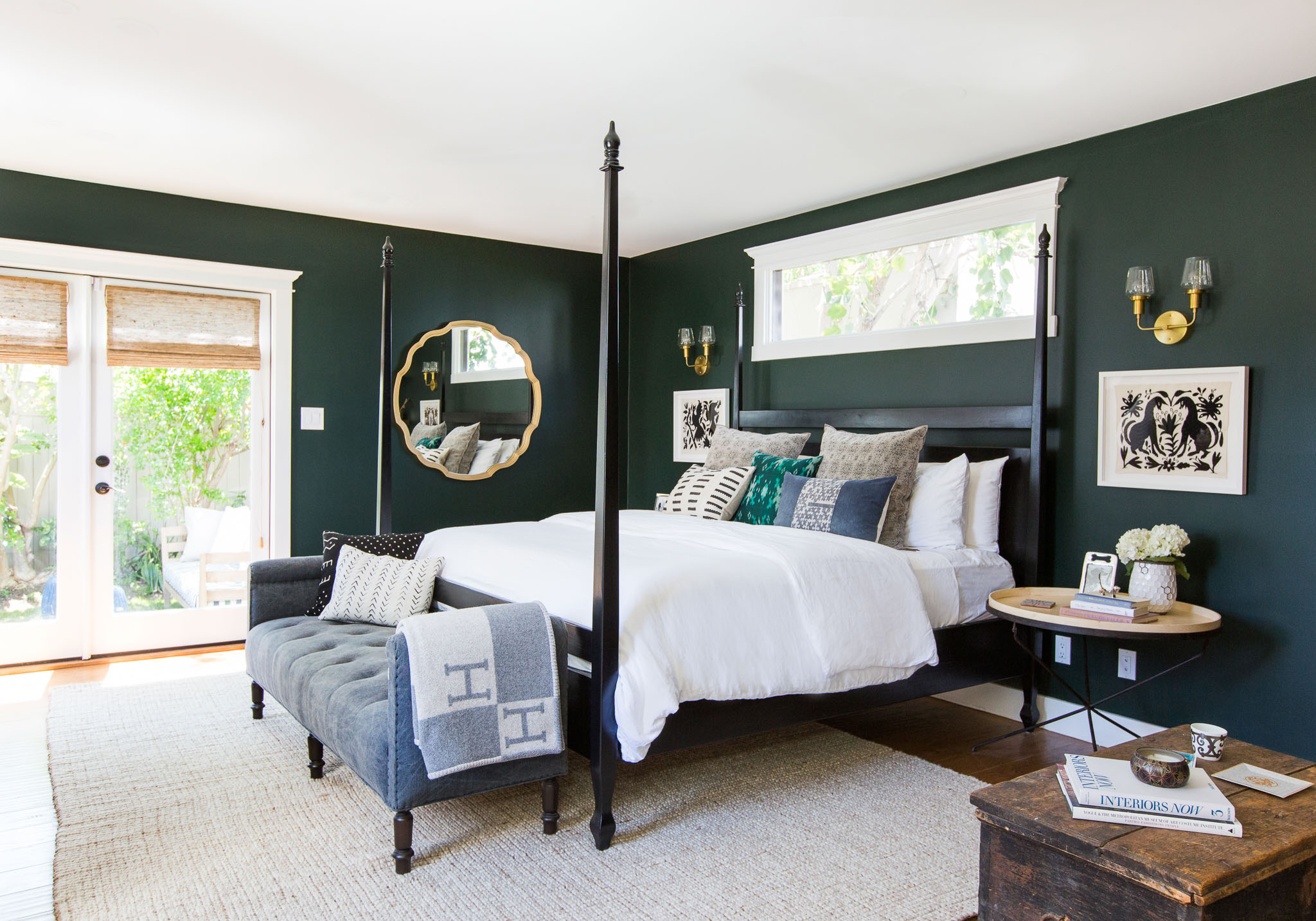 A master suite with four-poster bed, rich-toned walls and woven wood shades