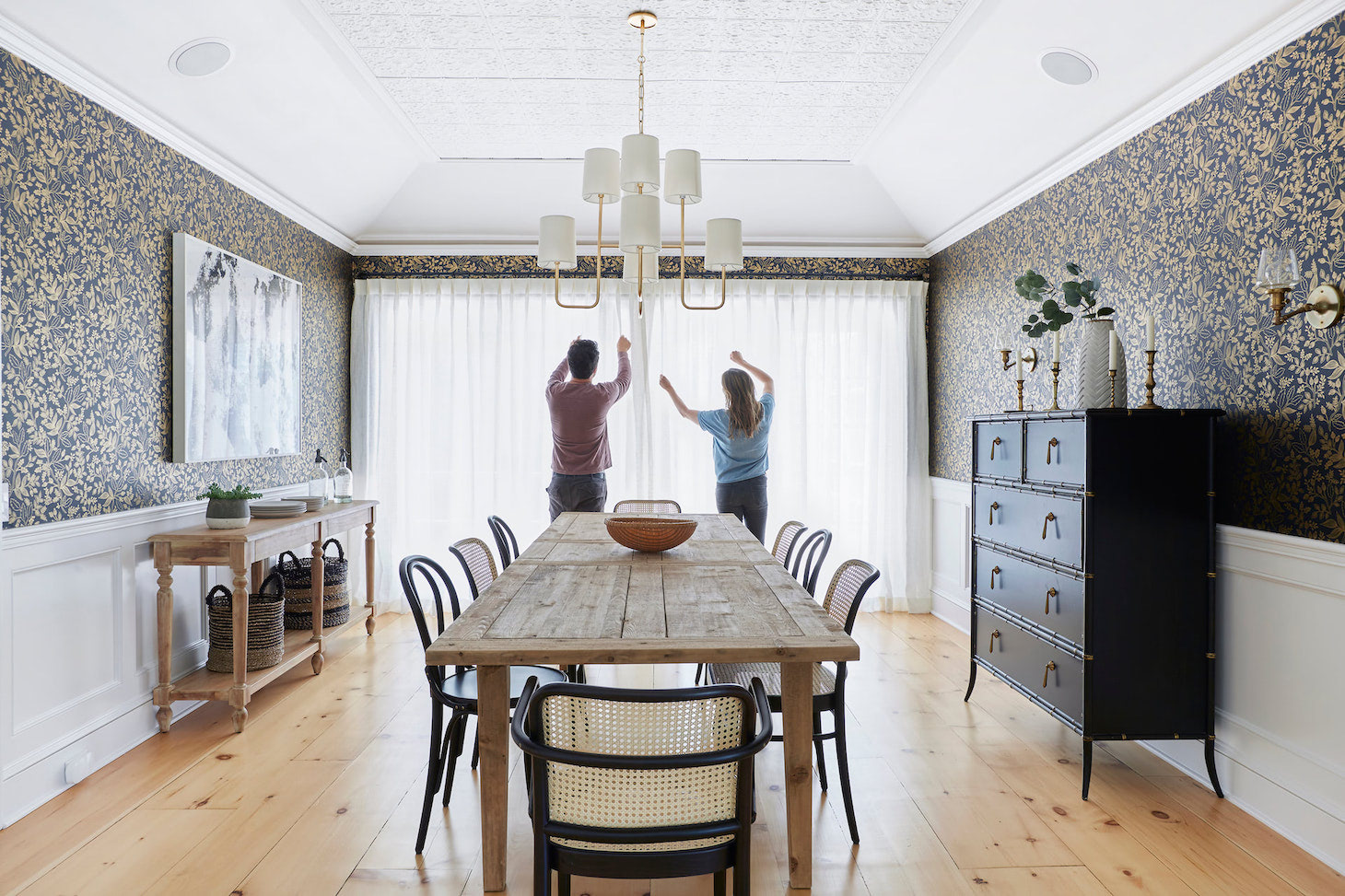 Haley Weidenbaum and her husband hanging white drapes in a dining room | Everhem