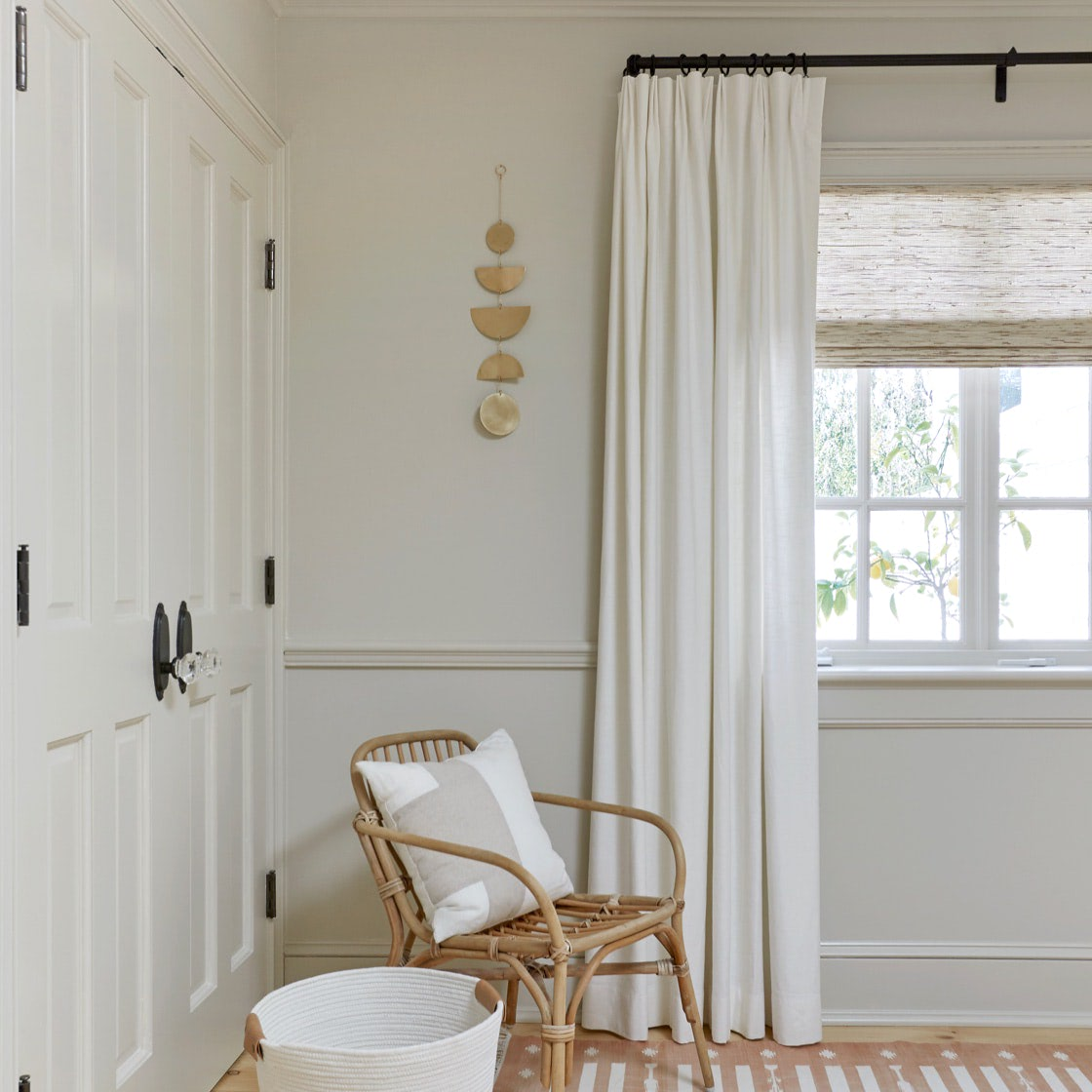 A room with custom drapes and roman shades covering a window | Everhem