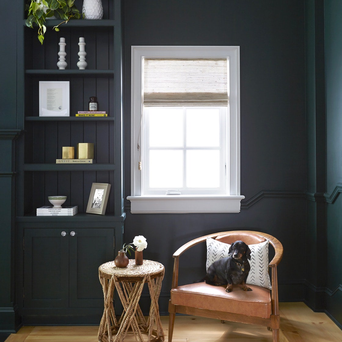A dark shelf unit next to a window with roman shades | Everhem