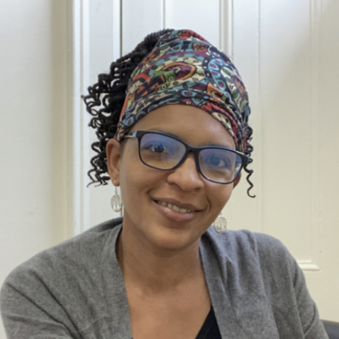 Image description: Shana sitting on a grey chair smiling with a white background. She is wearing black square-rimmed glasses with a colorful bandana on her head.