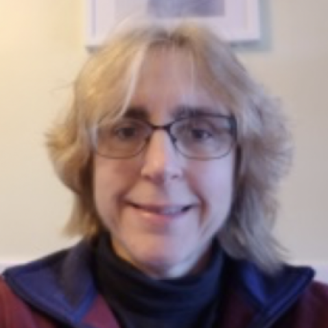 Carol is smiling at the camera with black-rimmed glasses. Her light blonde hair goes down to her shoulders. She is wearing a dark red sweater with a black shirt underneath. Her background is light yellow.